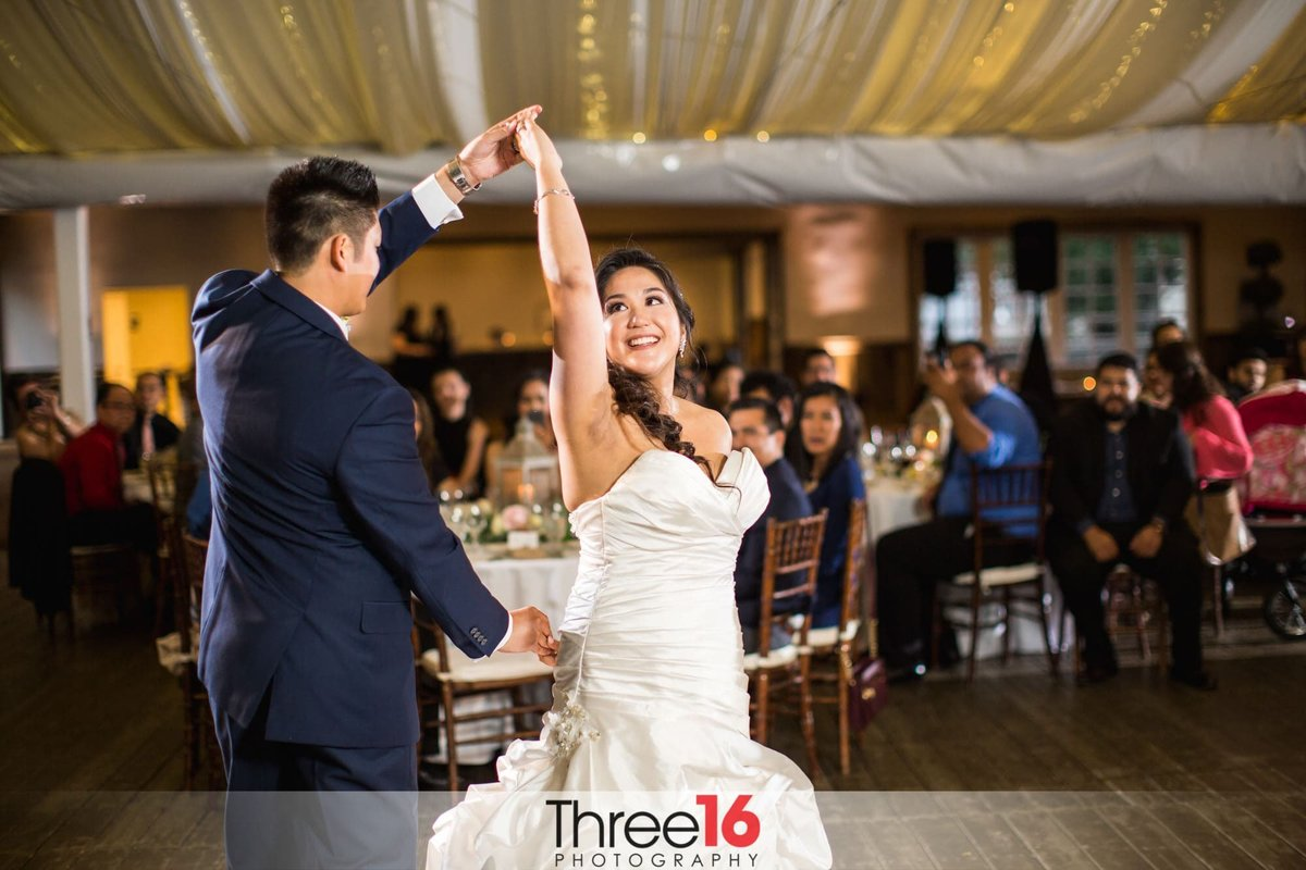 Bride twirls with her Groom on the dance floor during their first dance