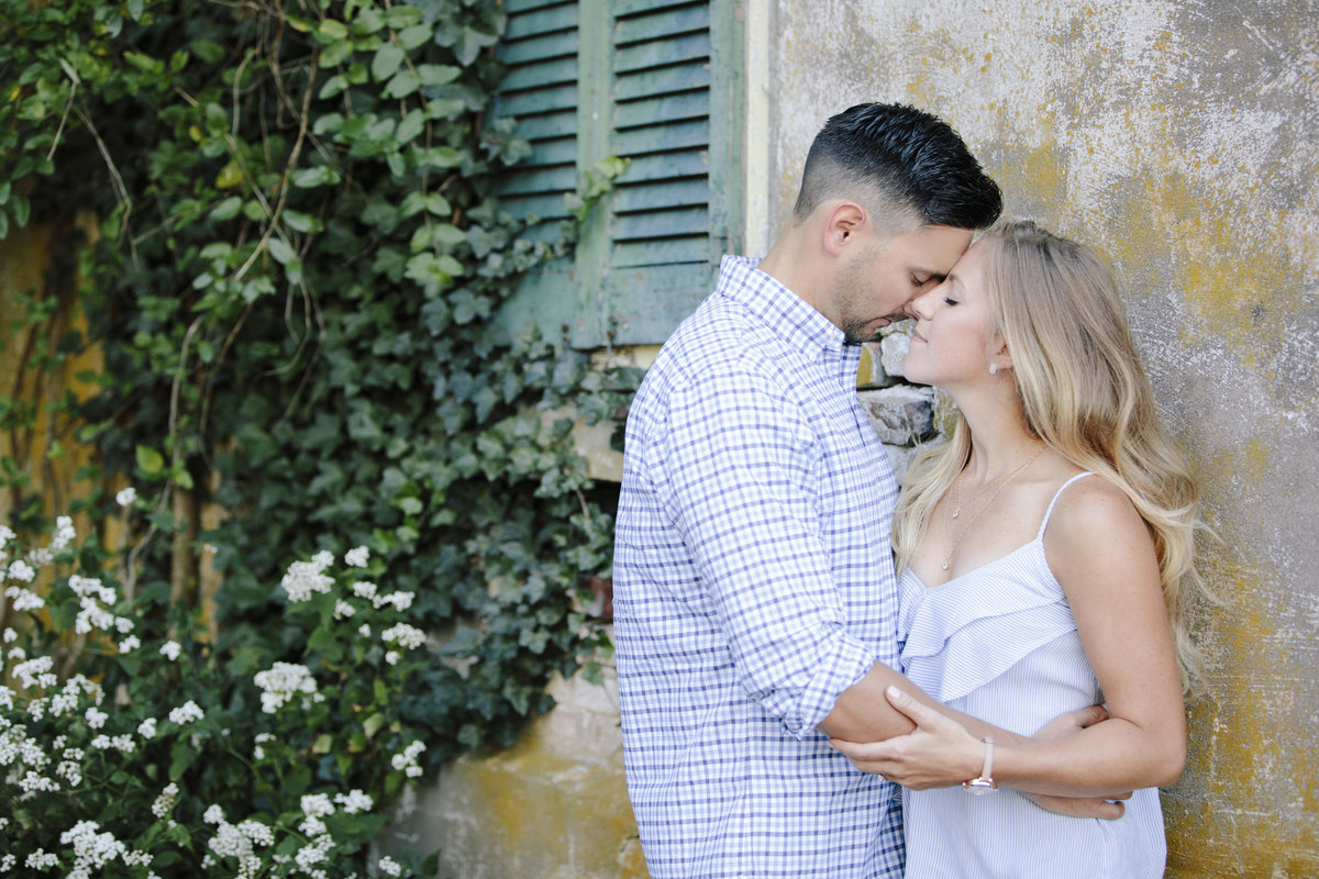 engaged couple kissing by old house at laurita winery