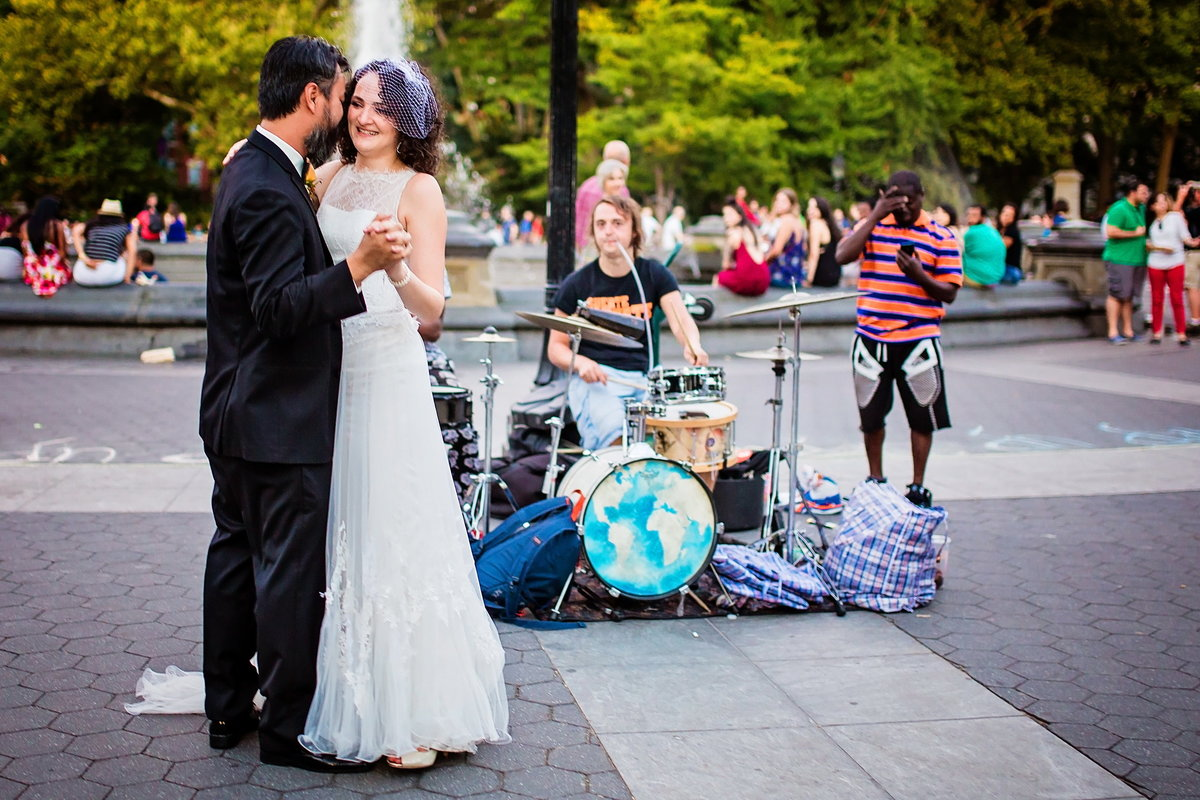 Bride and groom dance to street musicians in Washington Square Park, NY