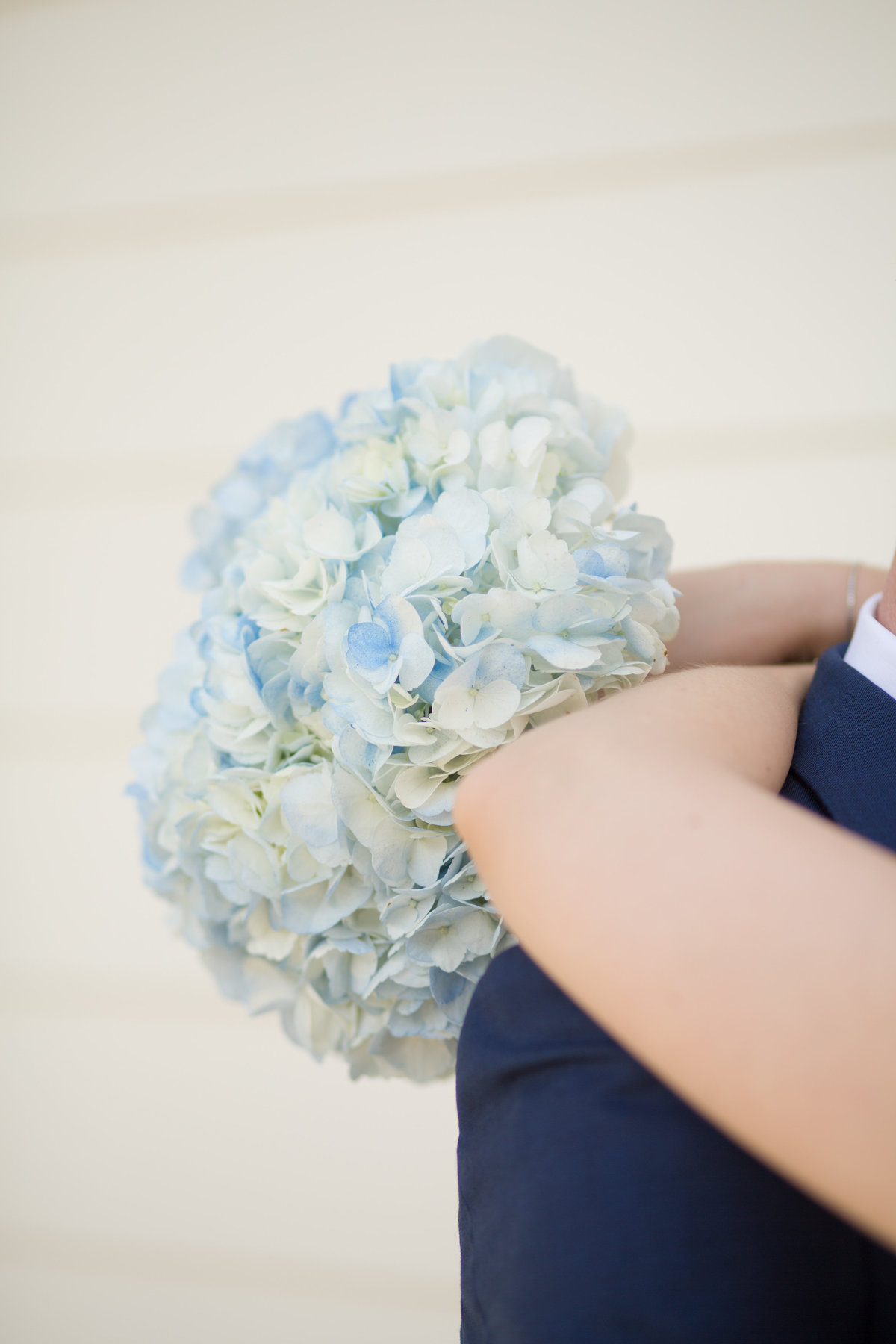 close up of a bride's arms around the groom's neck, she is holding her hydrangea bouquet