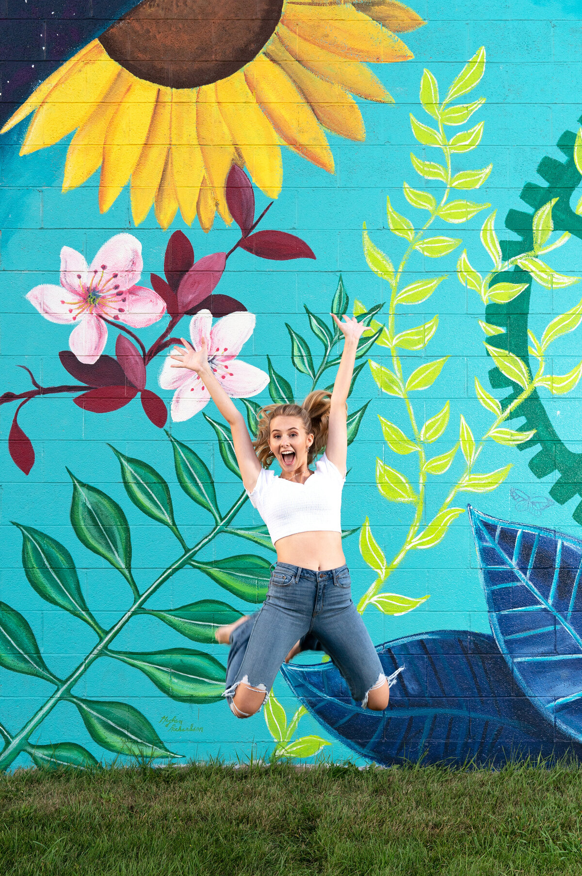 girl jumping by mural