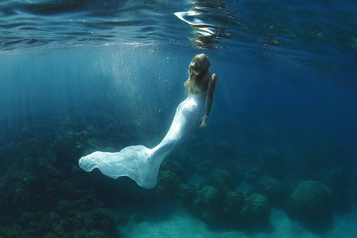 Maui bride swimming in the ocean wearing her wedding gown in Maui, Hawaii