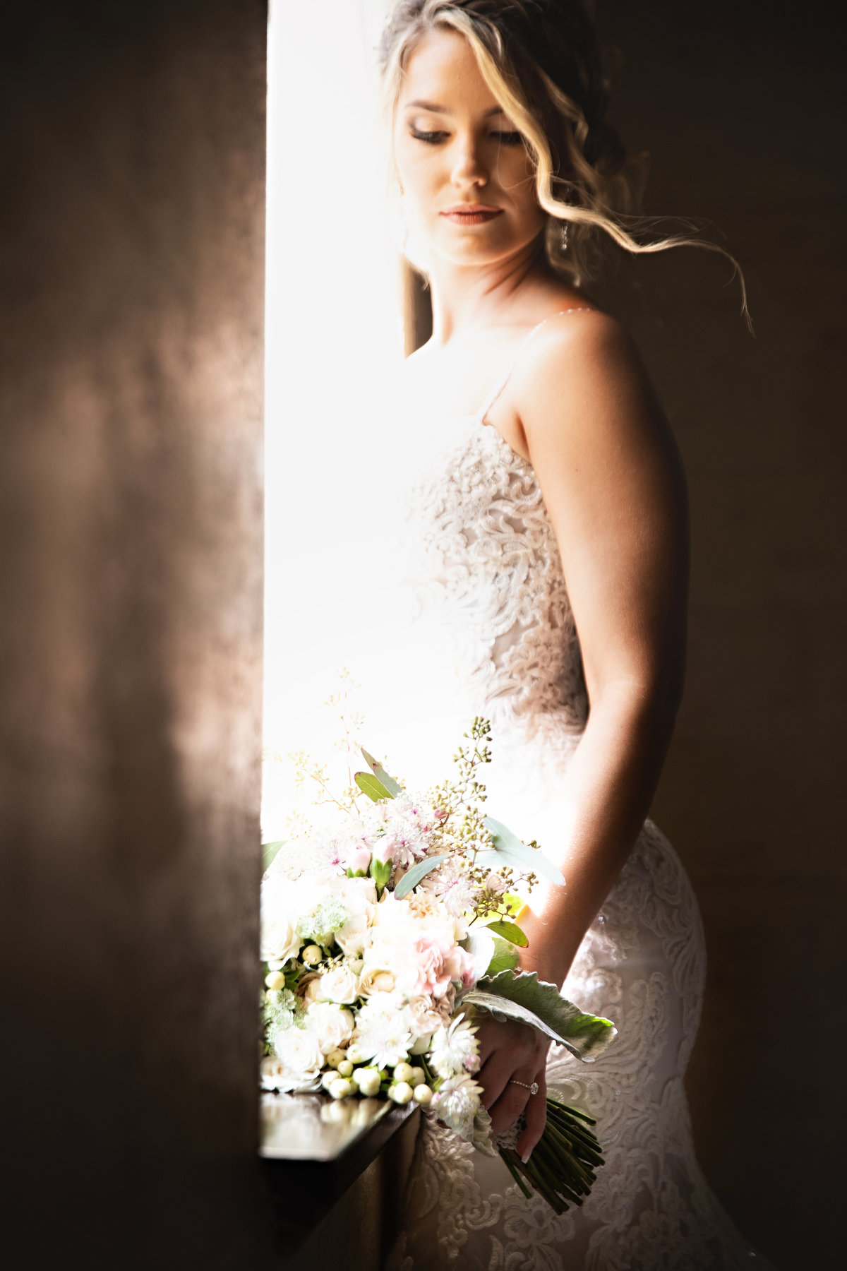 A picture of the bride in her beautiful wedding gown standing next to a window, looking down at her bouquet, as the sunlight shines in on her