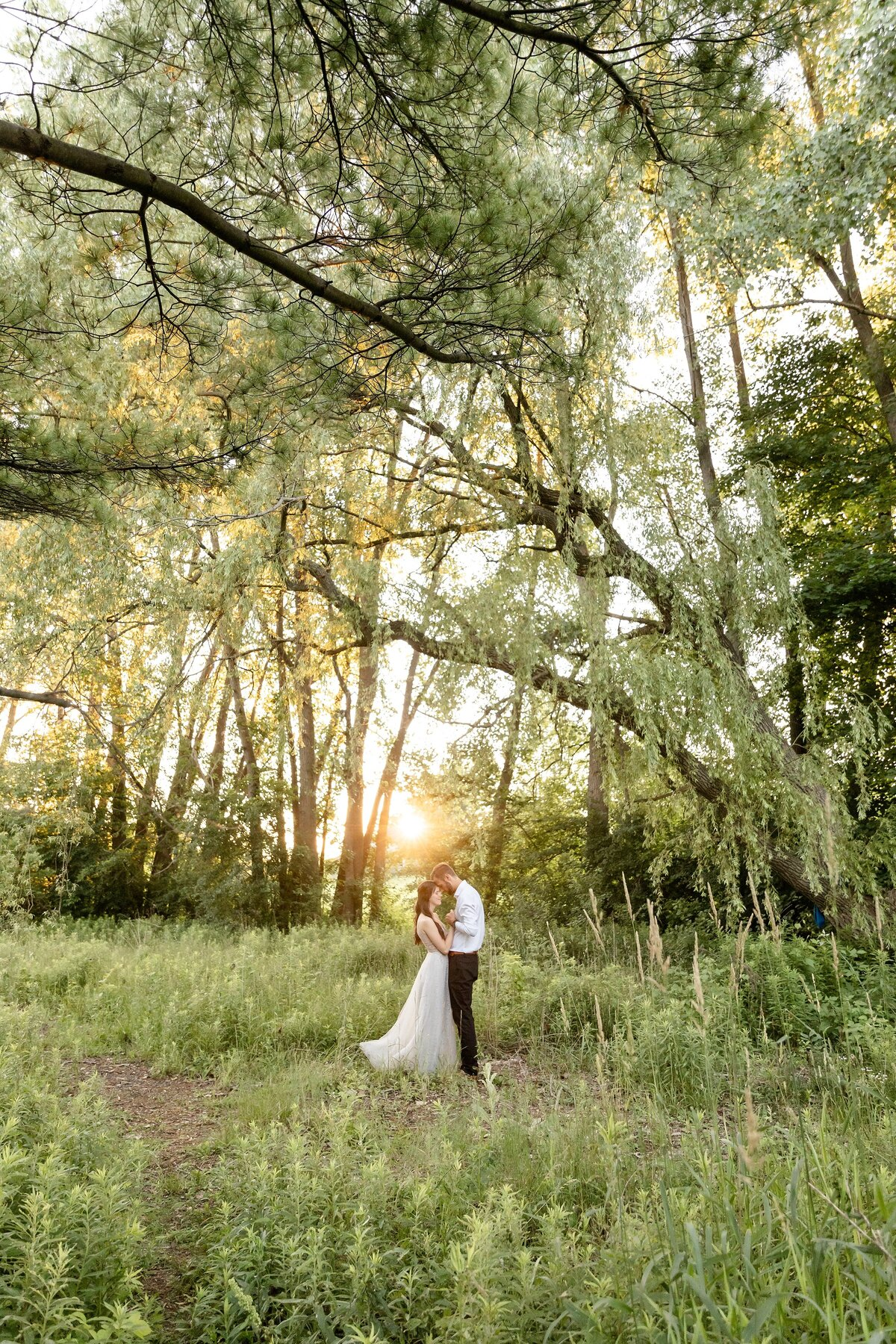 Couple-slow-dancing-with-their-foreheads-together-under-a-beautiful-tree-canopy-at-meadowlily-park-in-London-Ontario