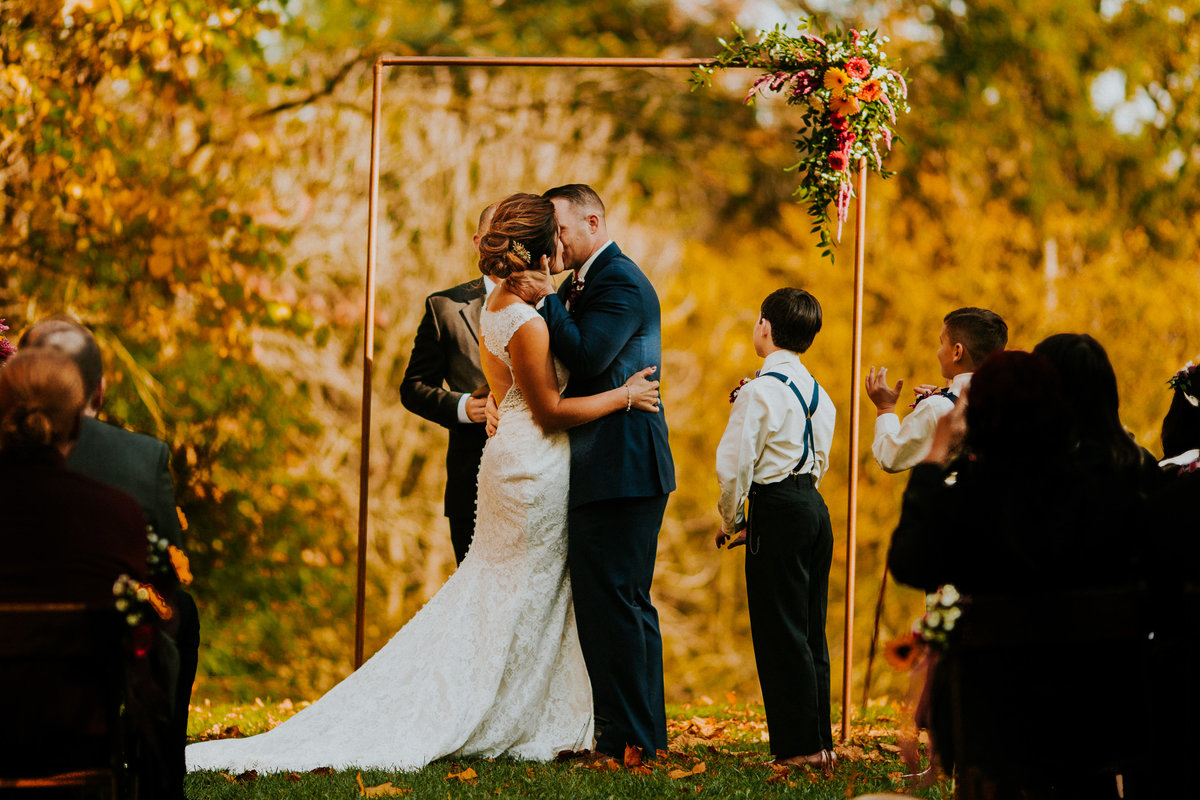 A first Kiss on the lawn of the glass pavilion with beautiful fall colors in the background