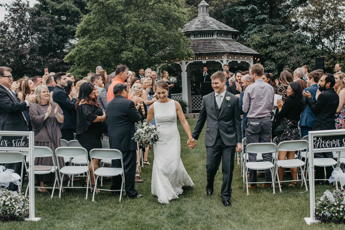 bride-and-groom-exiting-wedding-ceremony-ruffled-feathers-golf-club-lemont-il-adventurous-wedding-photographer-2
