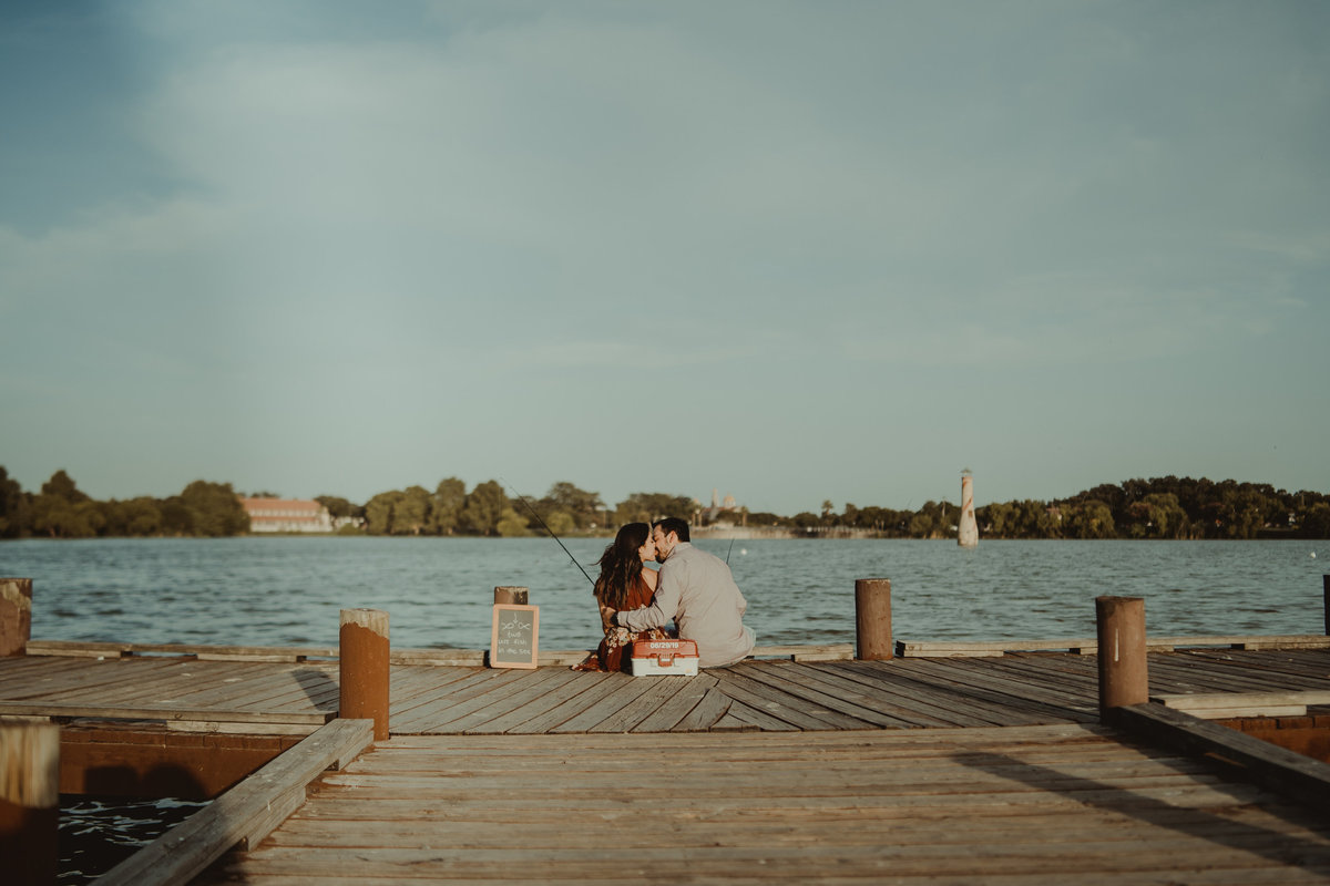 Couple kissing on the edge of a fishing pier on their engagement session by Expose The Heart Photography.