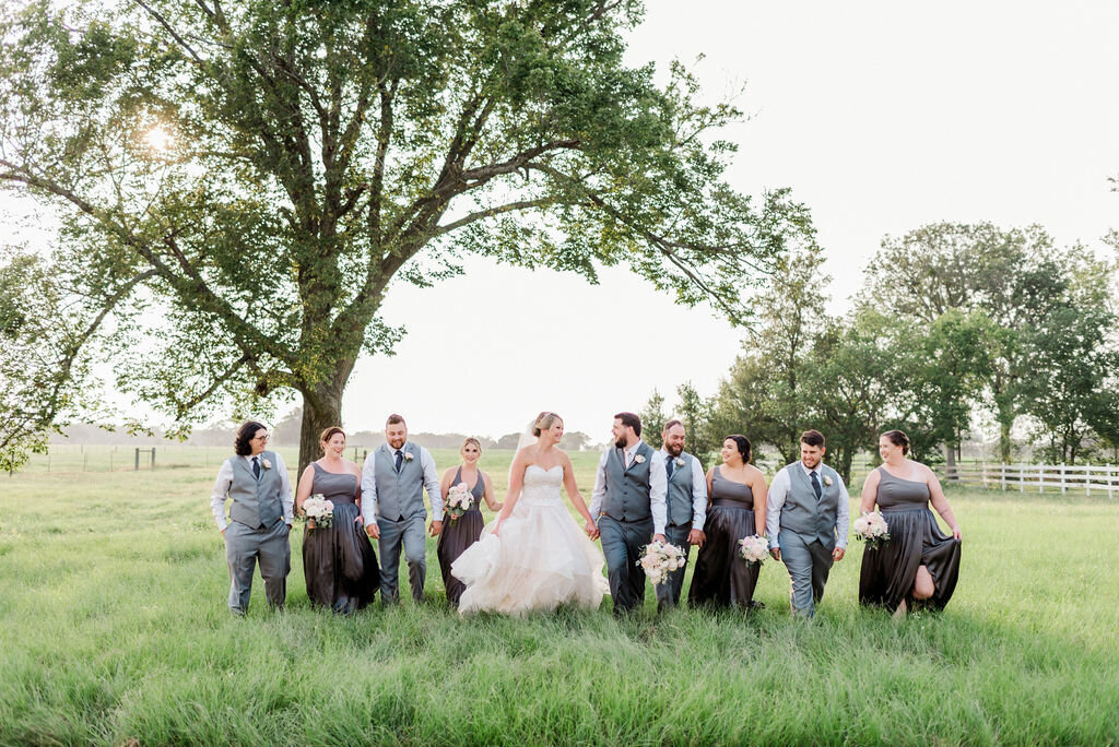 A bridal party walking through the Grand Texana fields with trees in the background and a sunset. The bridal party is laughing and smiling