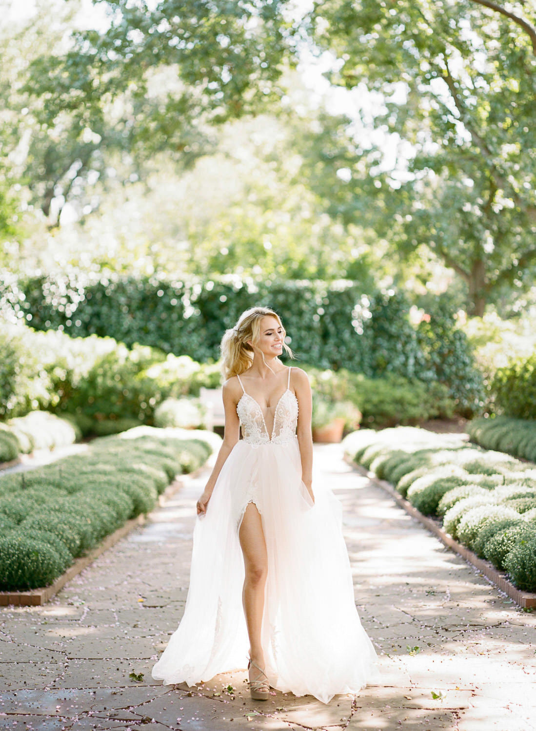 blonde bride in white wedding dress smiling in green garden