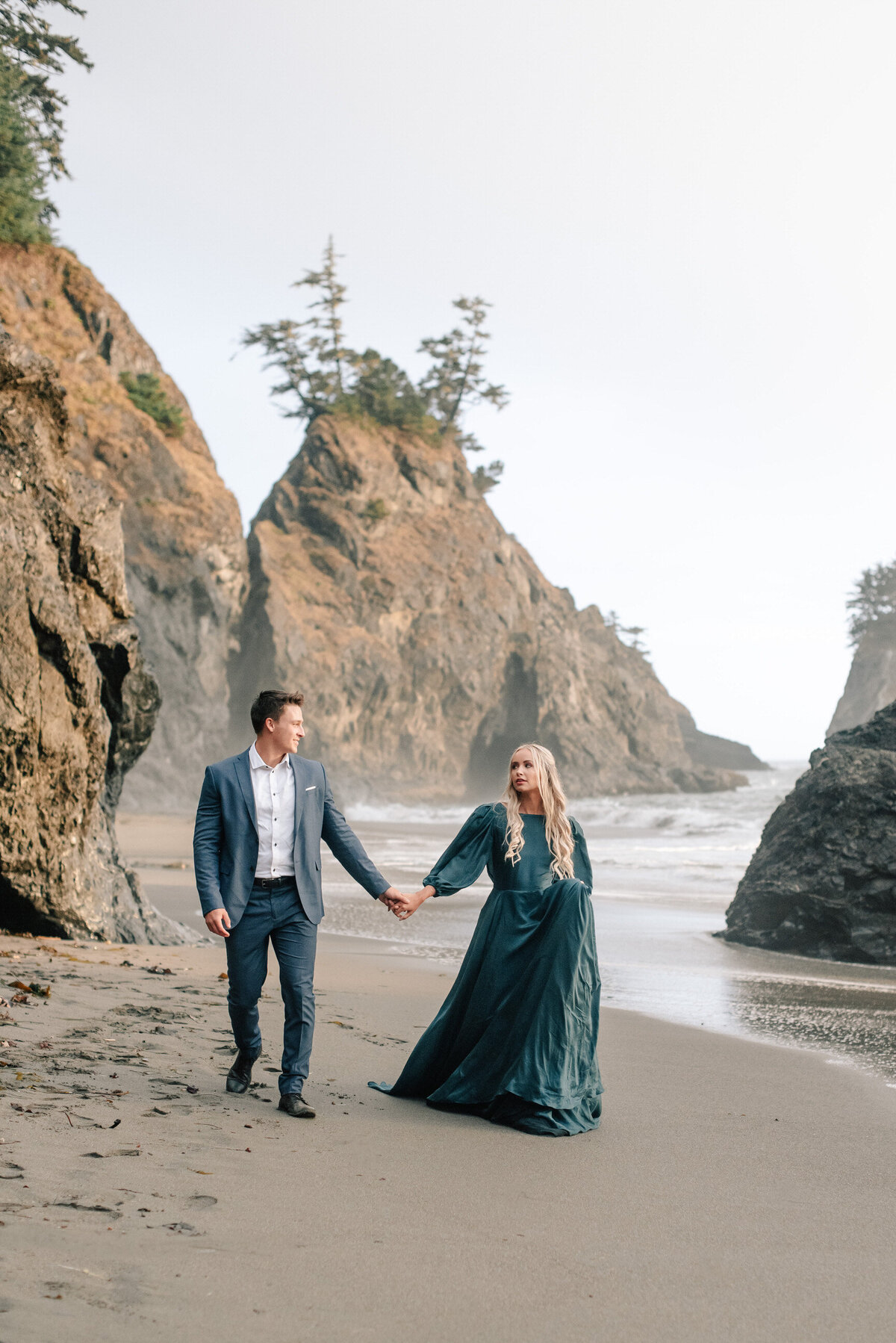 Couple walking on the beach in Brookings, Oregon featuring a green Emily Riggs dress