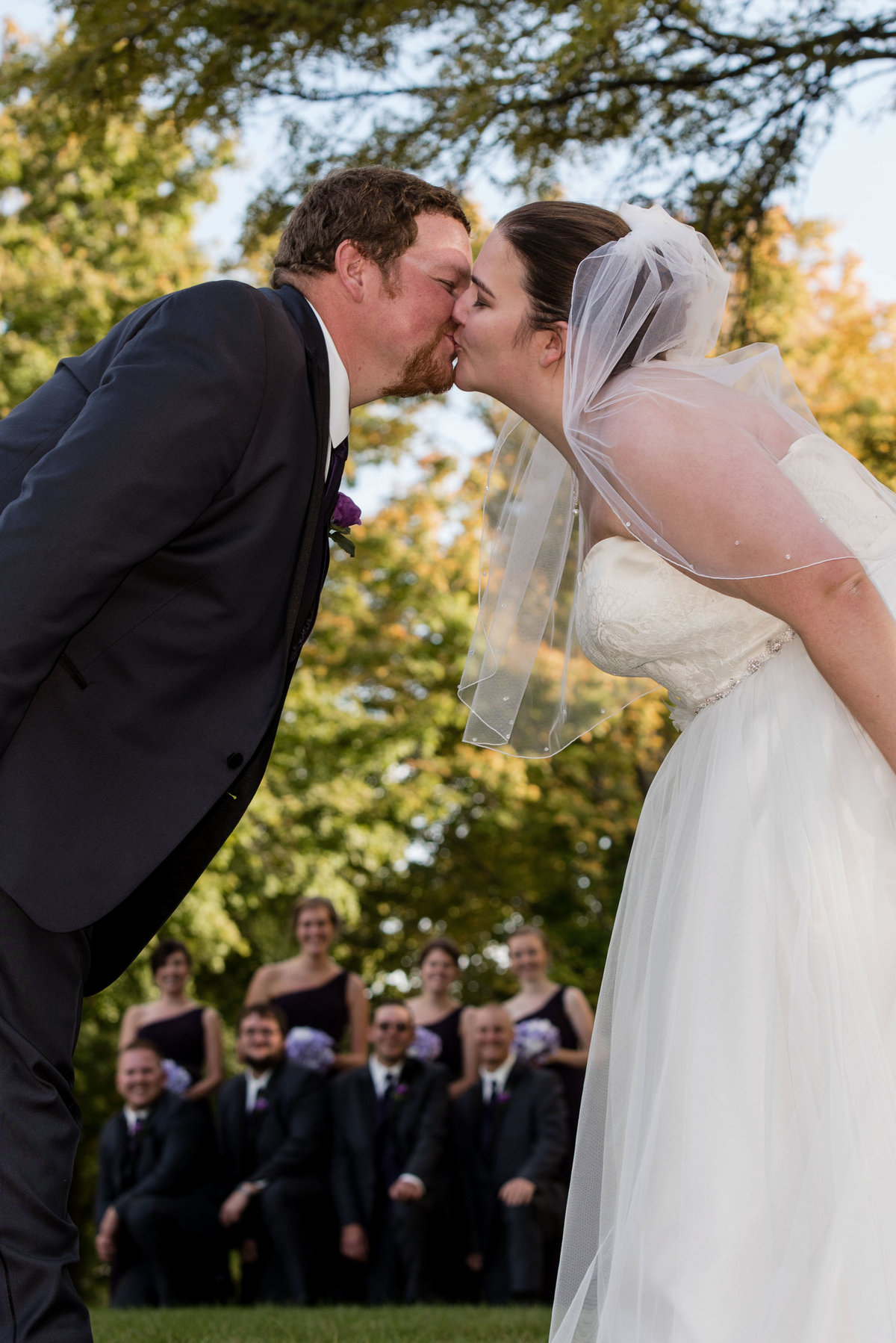 kiss with bridal party in background