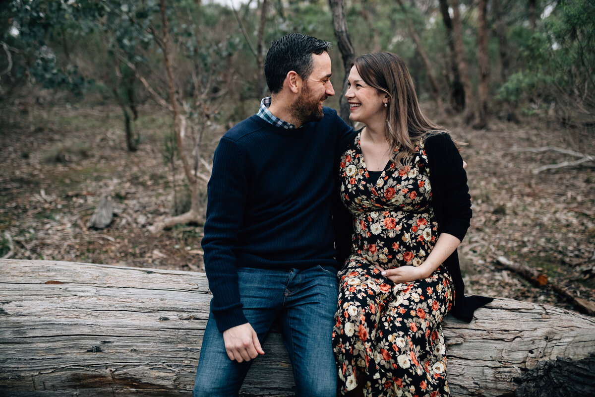 couple sitting on log outside Maternity photography Melbourne And So I Don't Forget Photographer