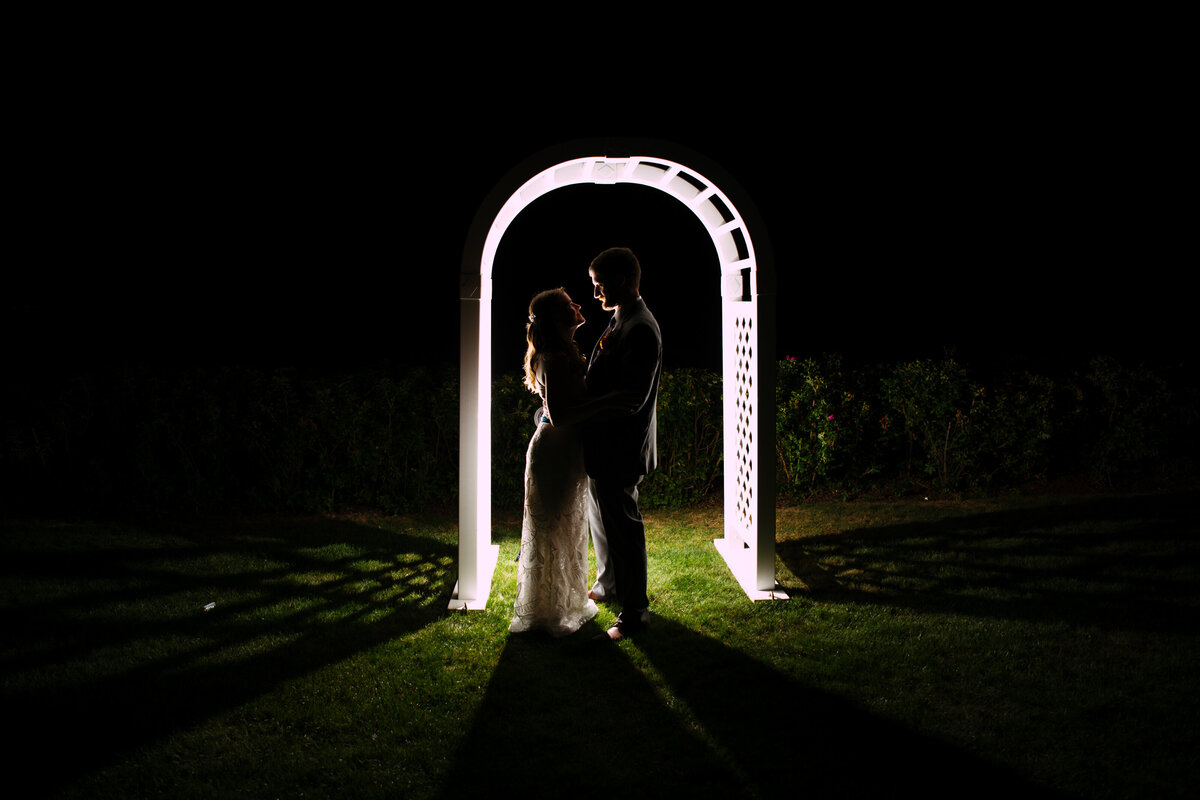 Silhouette night photo of bride and groom under archway at Massachusetts wedding