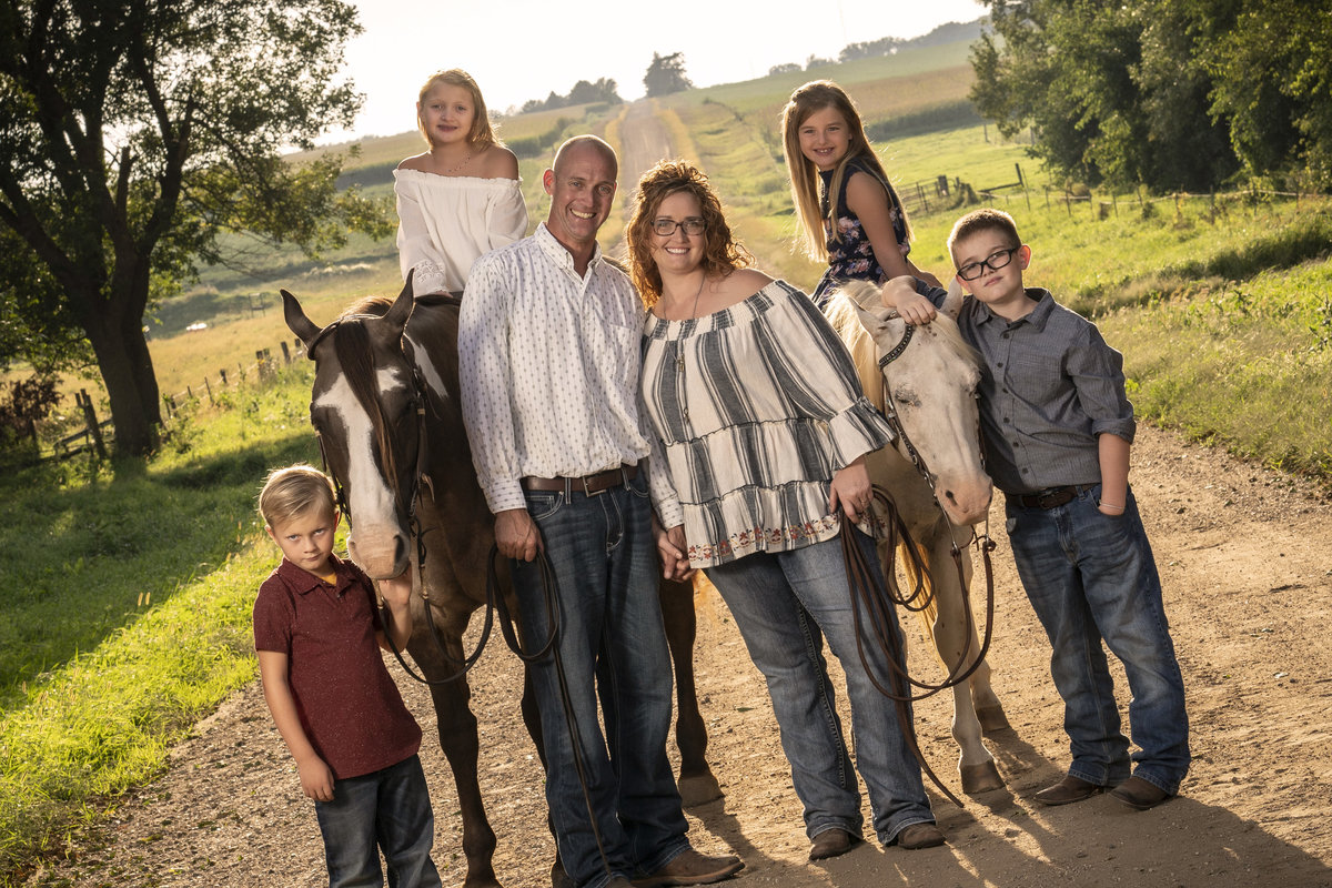 sioux falls family session portrait with horses on dirt road south dakota