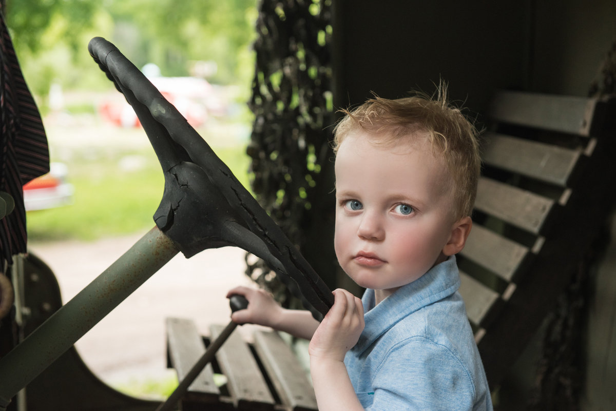 Little boy sitting in old car