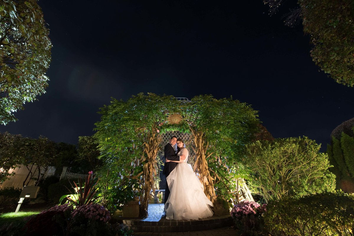 Night photo of bride and groom at the gardens at Watermill Caterers