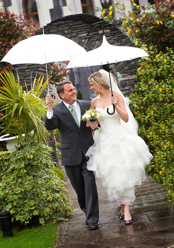 Bride wearing an A-line wedding dress with tulle ruffles and navy wedding shoes walking with her father, while holding white umbrellas in the rain at the Muckross Park Hotel