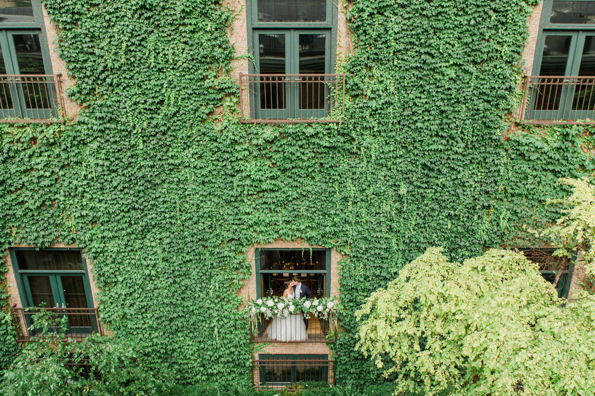 couple kissing on a balcony surrounded by ivy