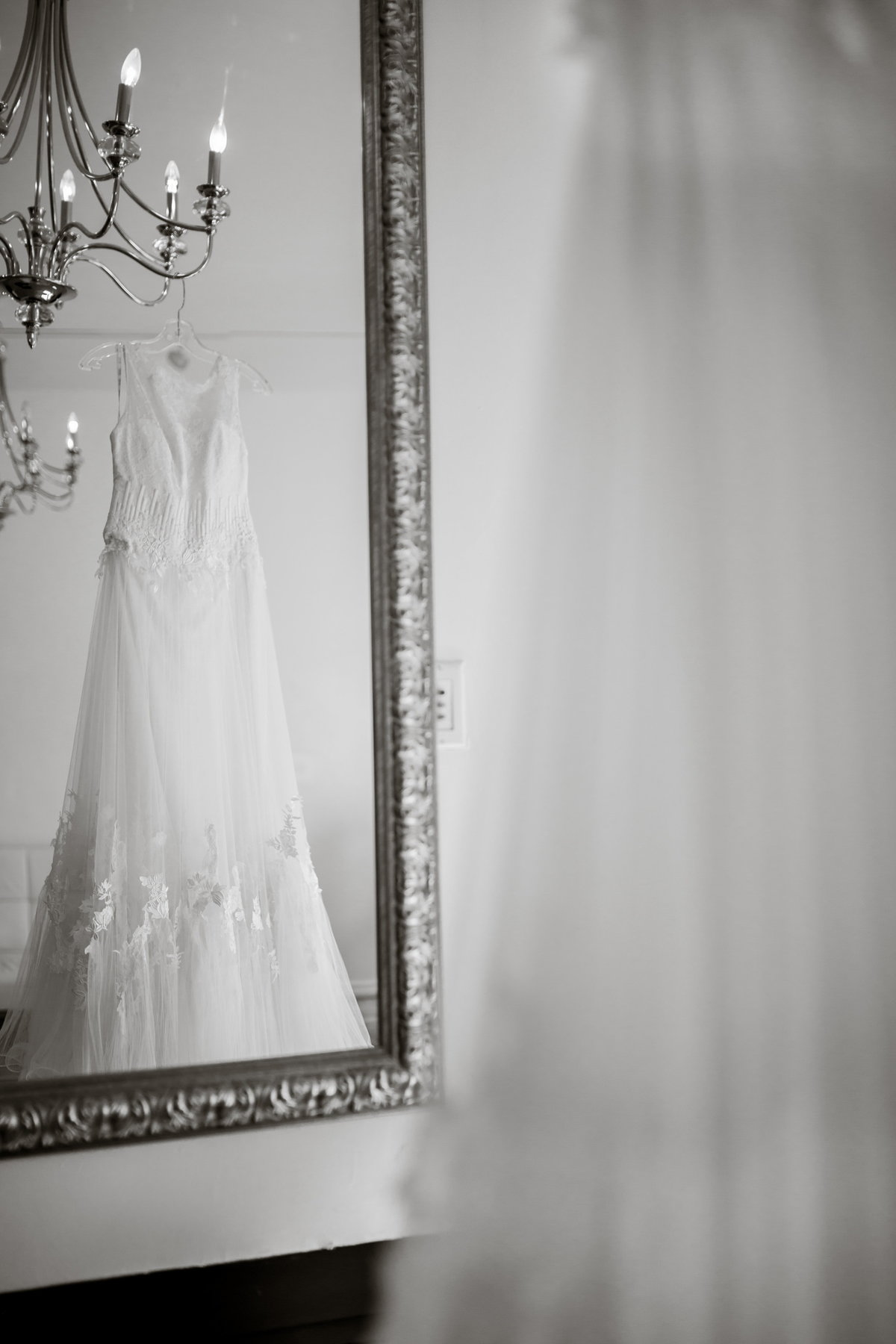 Black and white photo of wedding dress hanging from chandelier being reflected in a wall mirror