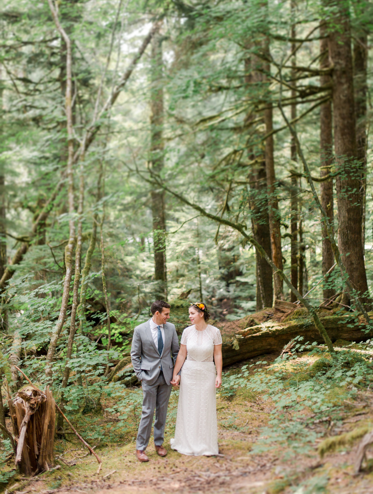 bride and groom stand together in the forest of mount rainier national park