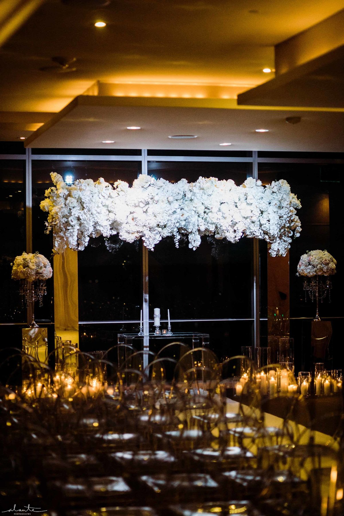 All white floral on a mirrored wedding arch with phalaenopsis orchids.