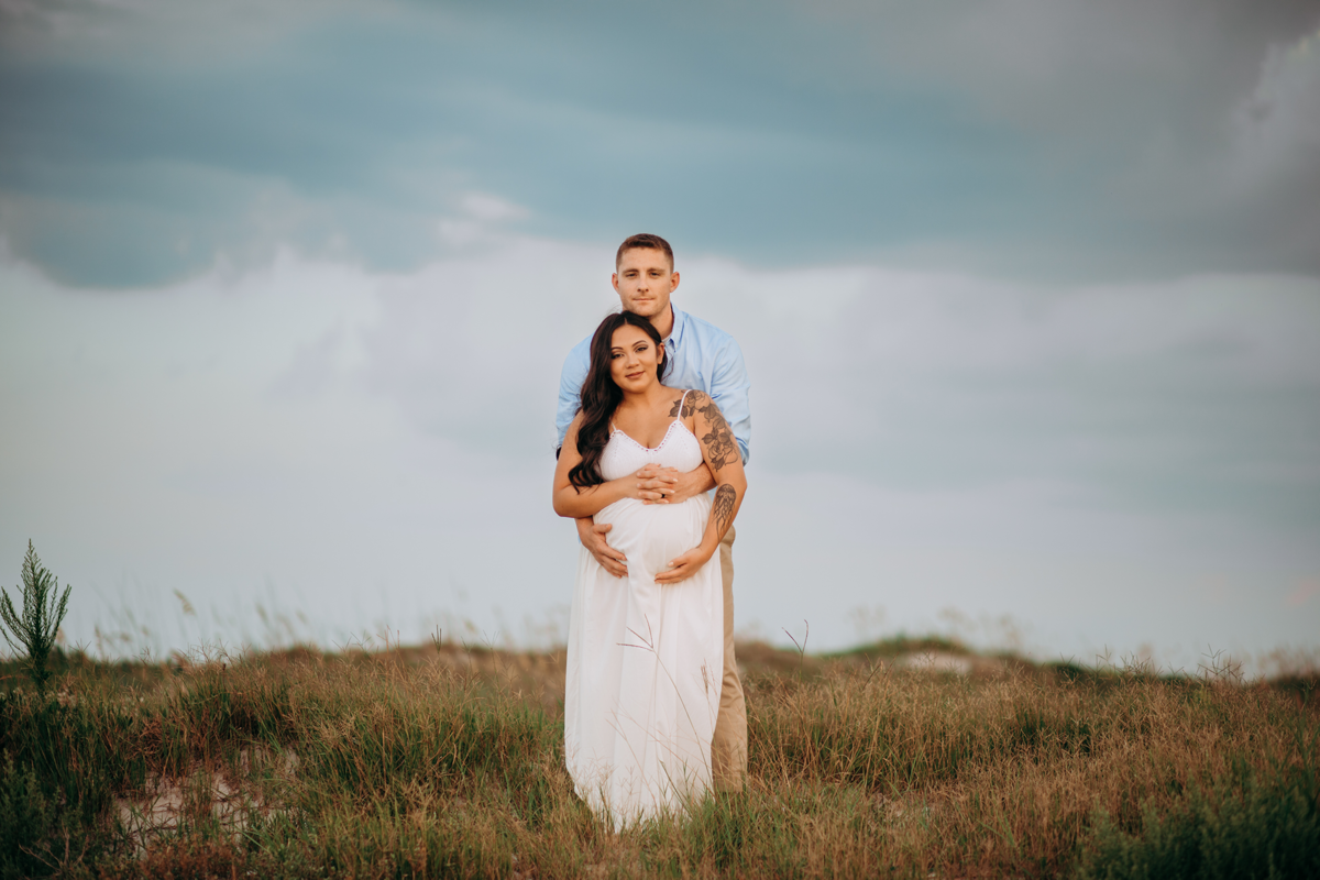 Okinawa Maternity Photography, man standing with his arms around his wife