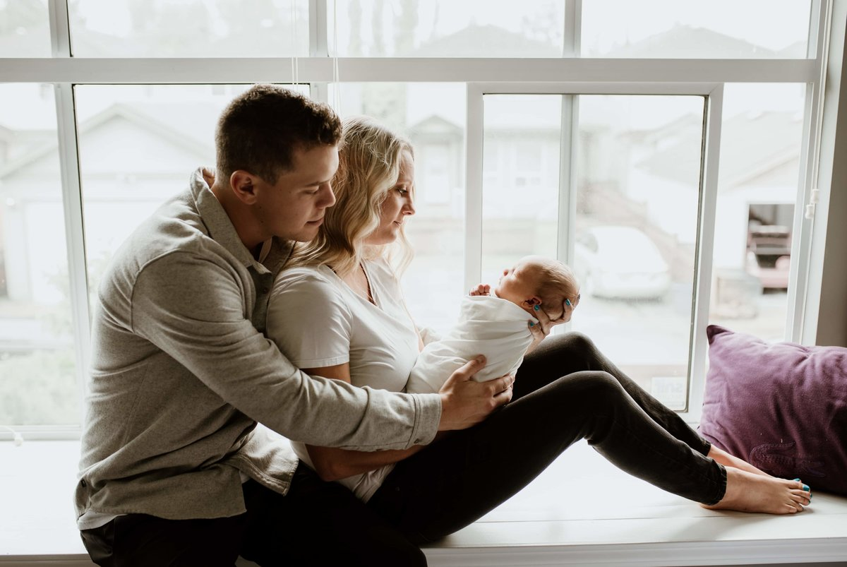 family with newborn sitting by window