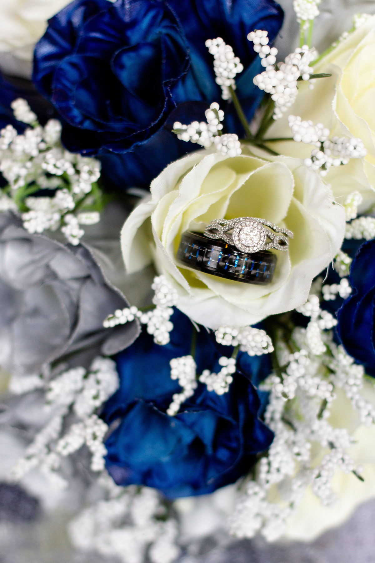 Engagement ring and wedding rings, both bride and groom, focused on in white, blue and silver bridal bouquet in Lakeland, Florida