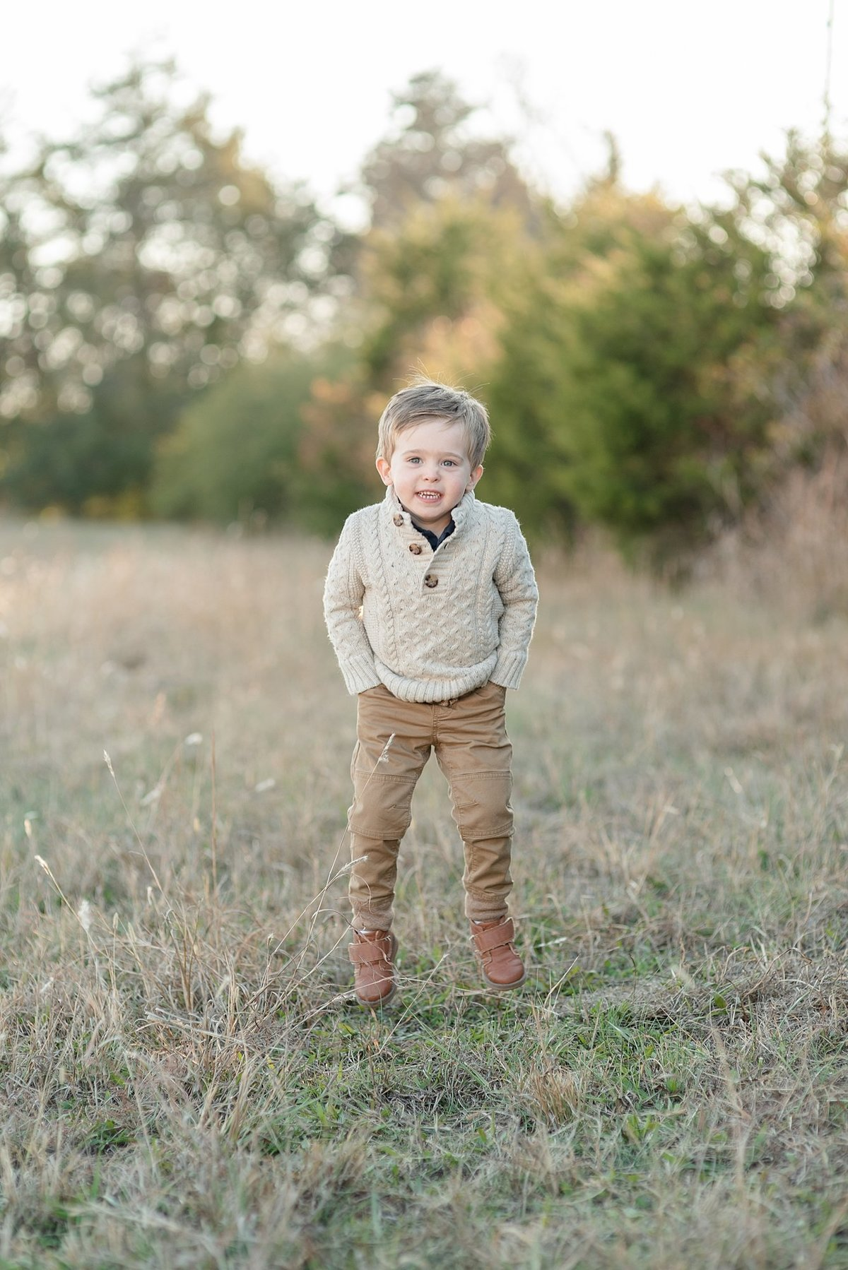 A toddler is jumping in the air in the field for a family portrait session in Nashville