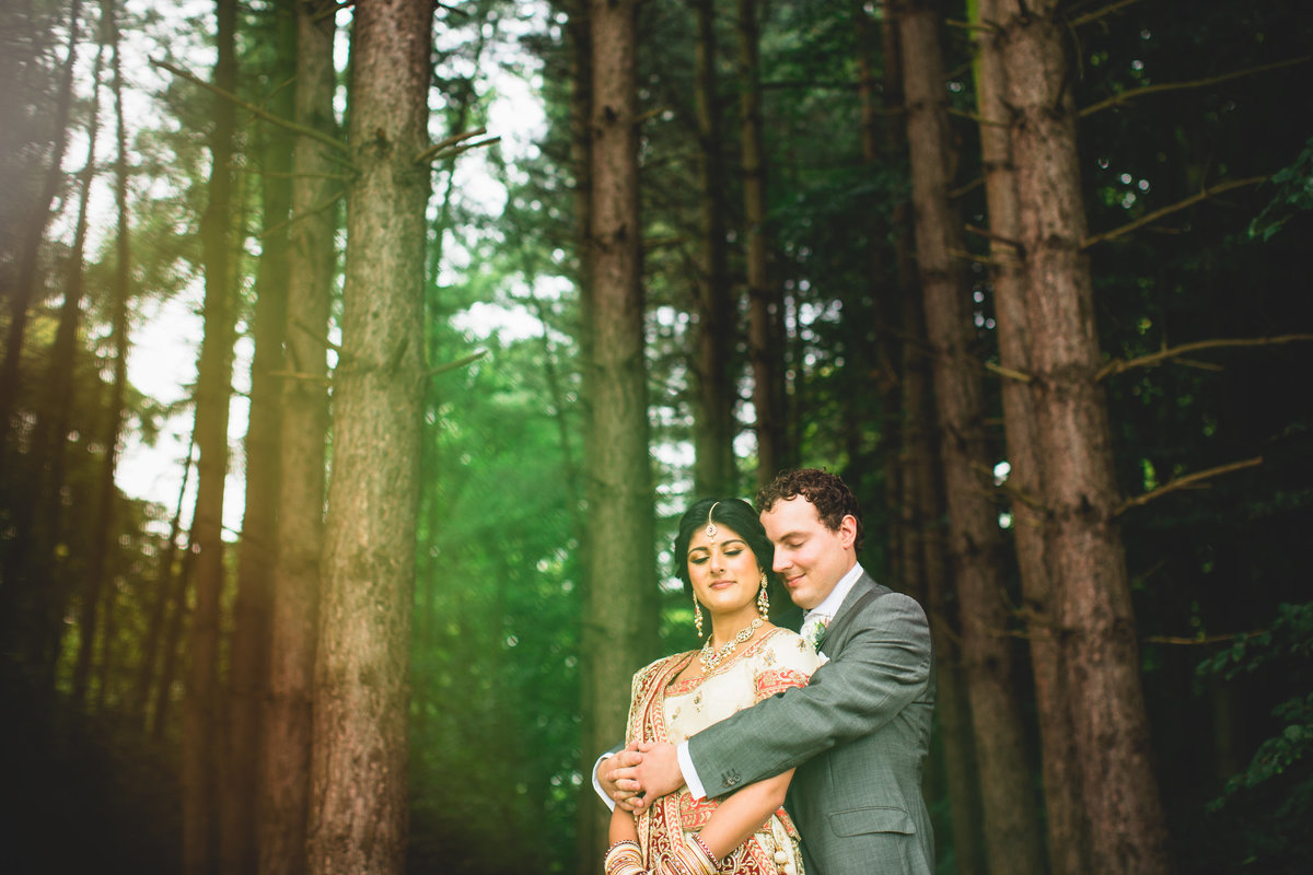 bride and groom at asian wedding in woods at knowsley hall