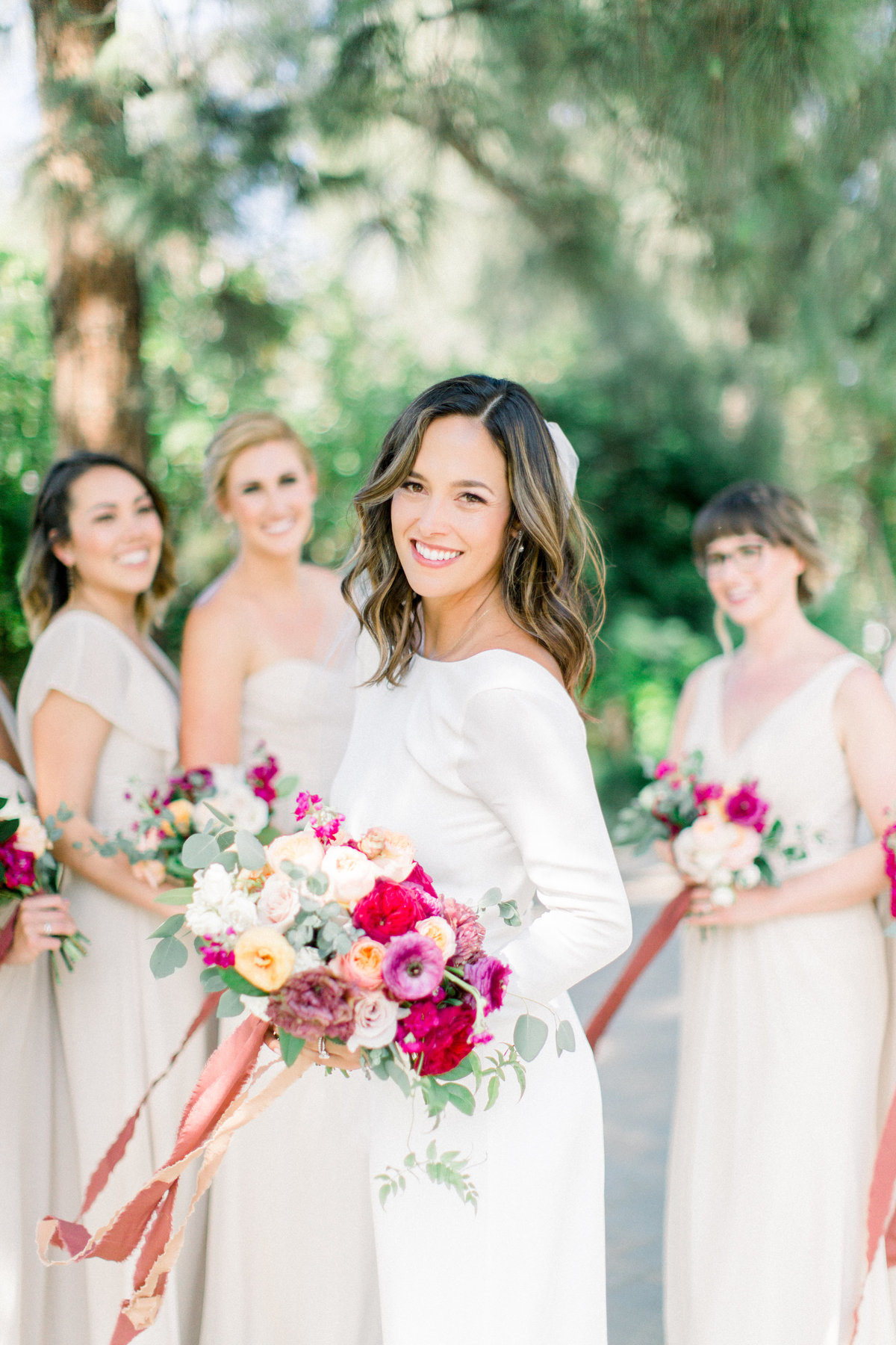 bride with long sleeve white wedding dress and mauve and orange bridal bouquet wedding portrait at Maravilla Gardens
