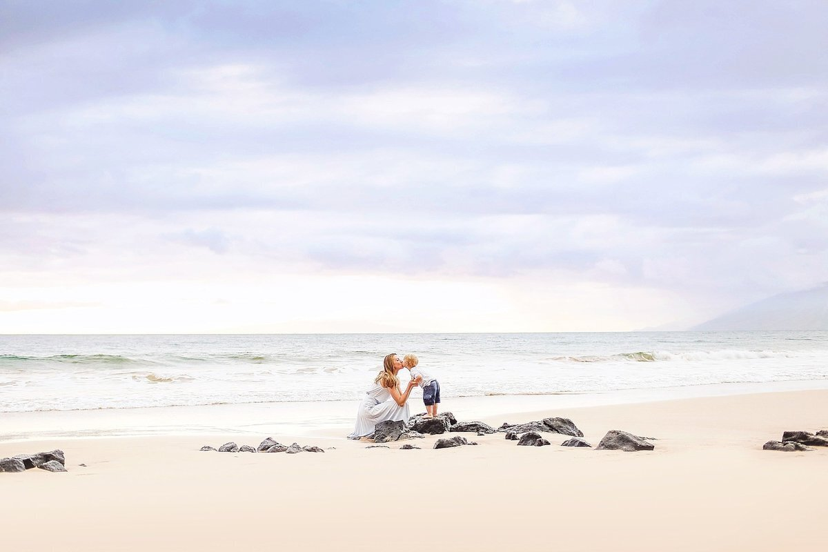 Little boy standing on lava rock kisses mother at the beach