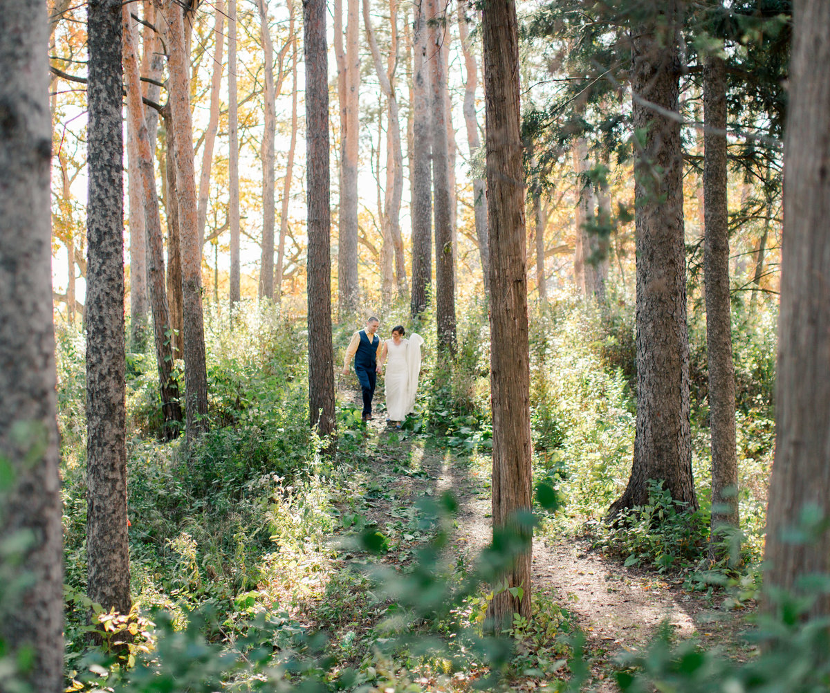 among tall pines in the fall bride and groom walk together through the forest