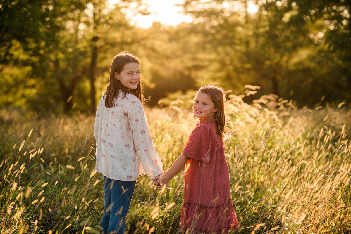 Des-Moines-Iowa-Family-Photographer-Theresa-Schumacher-Photography-Golden-Hour-Grass-Sisters-Looking-Back