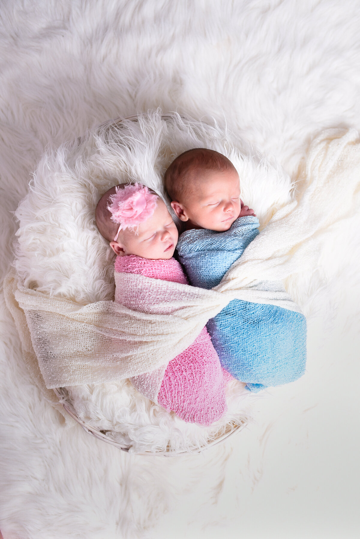 Beautiful Mississippi newborn photography: Twin newborns wrapped in pink and blue