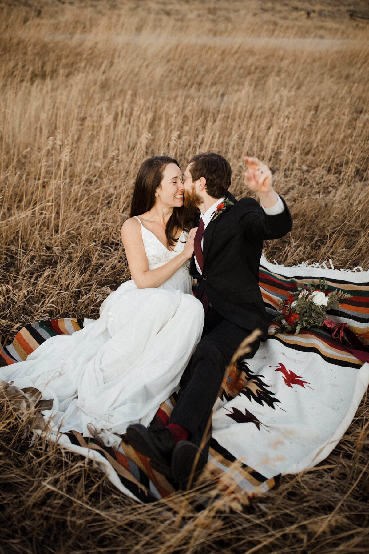 A bride and groom sit on a rustic blanket in a field kissing and waving a hand at the camera