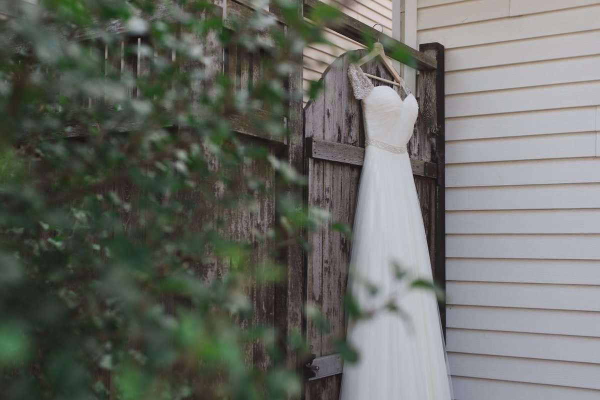 dress hanging from wooden fence