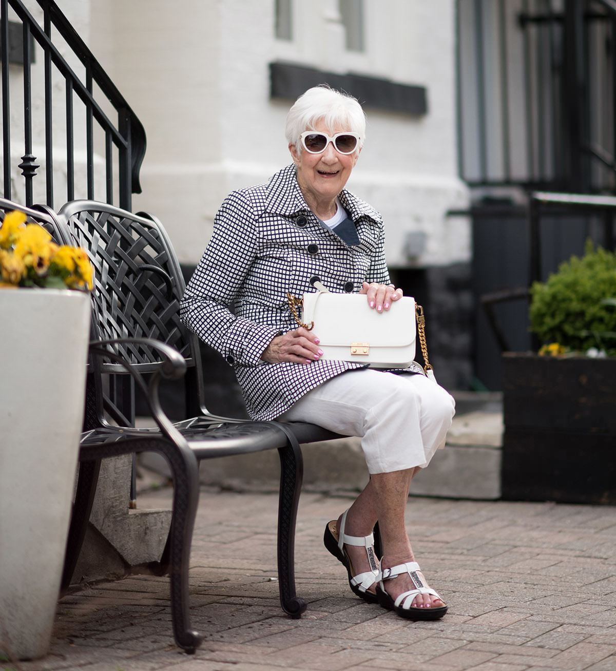 old woman sitting on bench modelling a purse