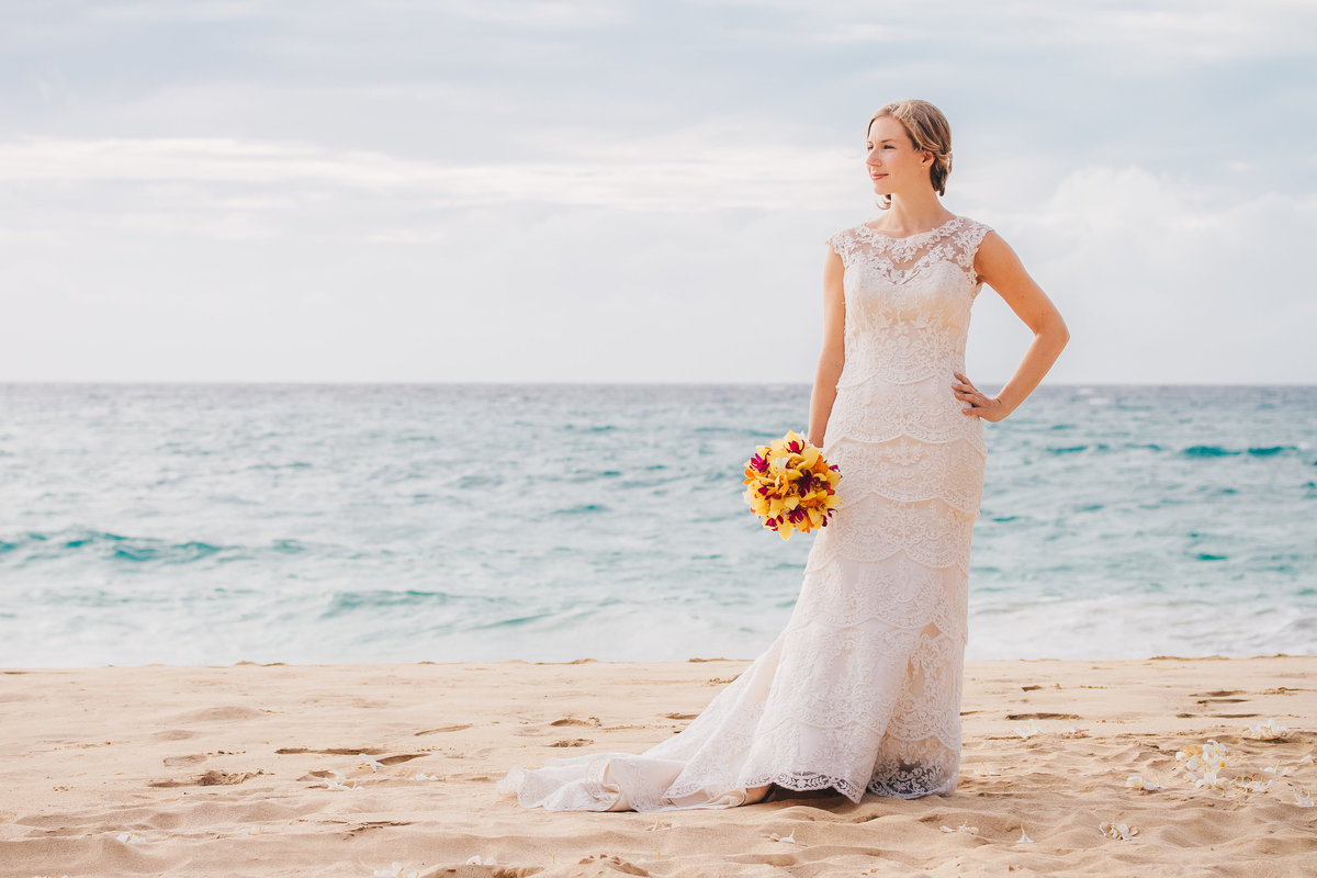 Bride on Kauai  beach with tropical bouquet.