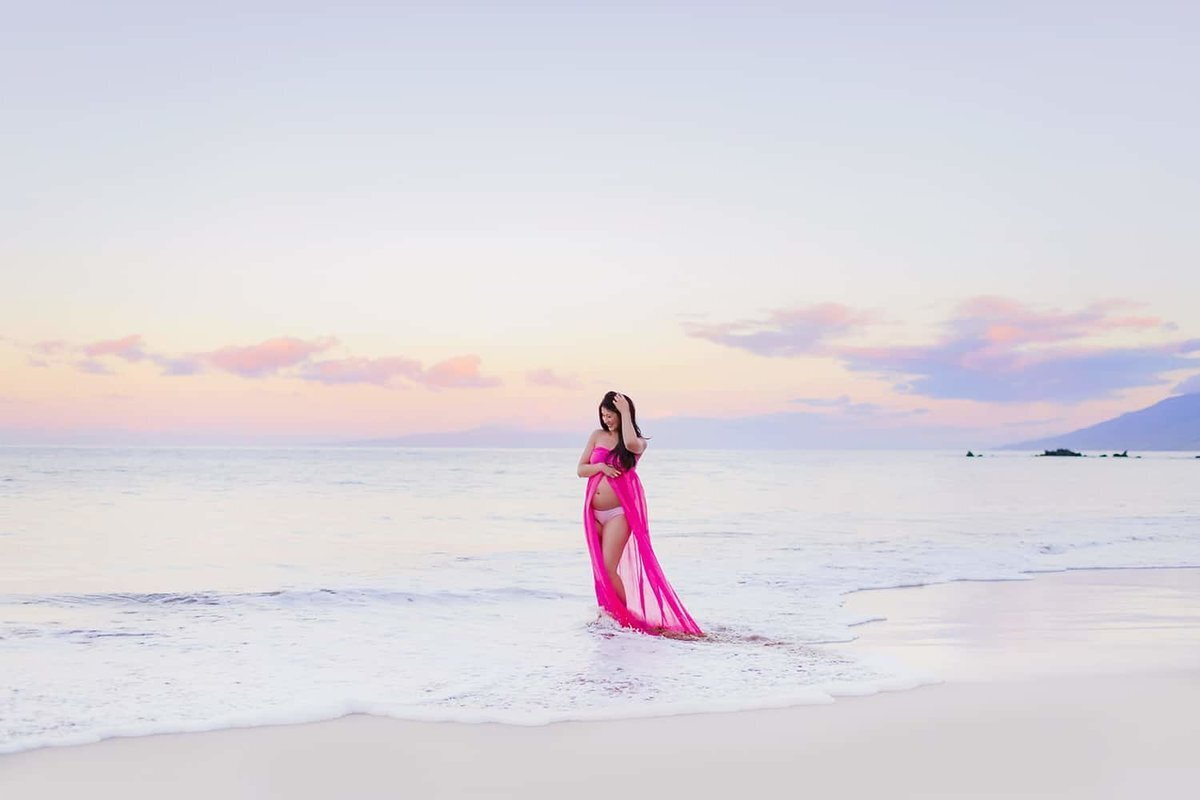 Woman wearing a bright pink maternity gown poses on the beach at sunset in Hawaii