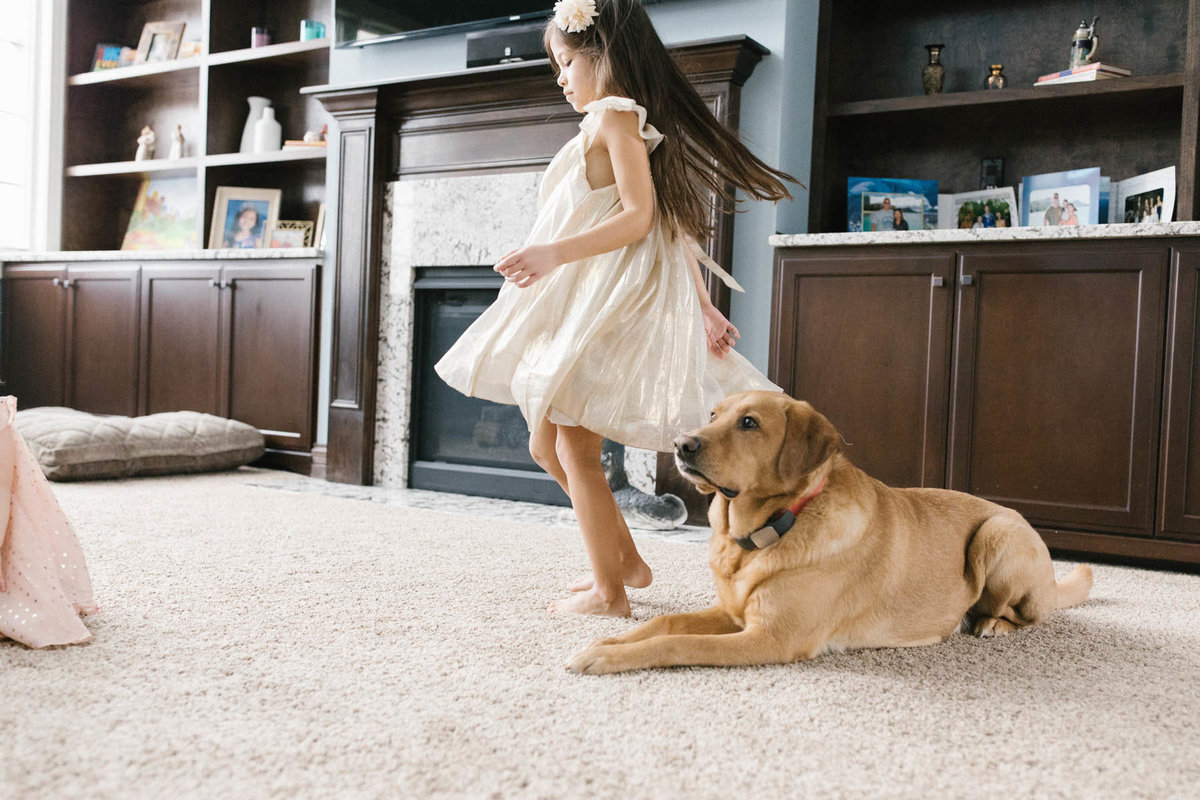 little girl dancing around her puppy