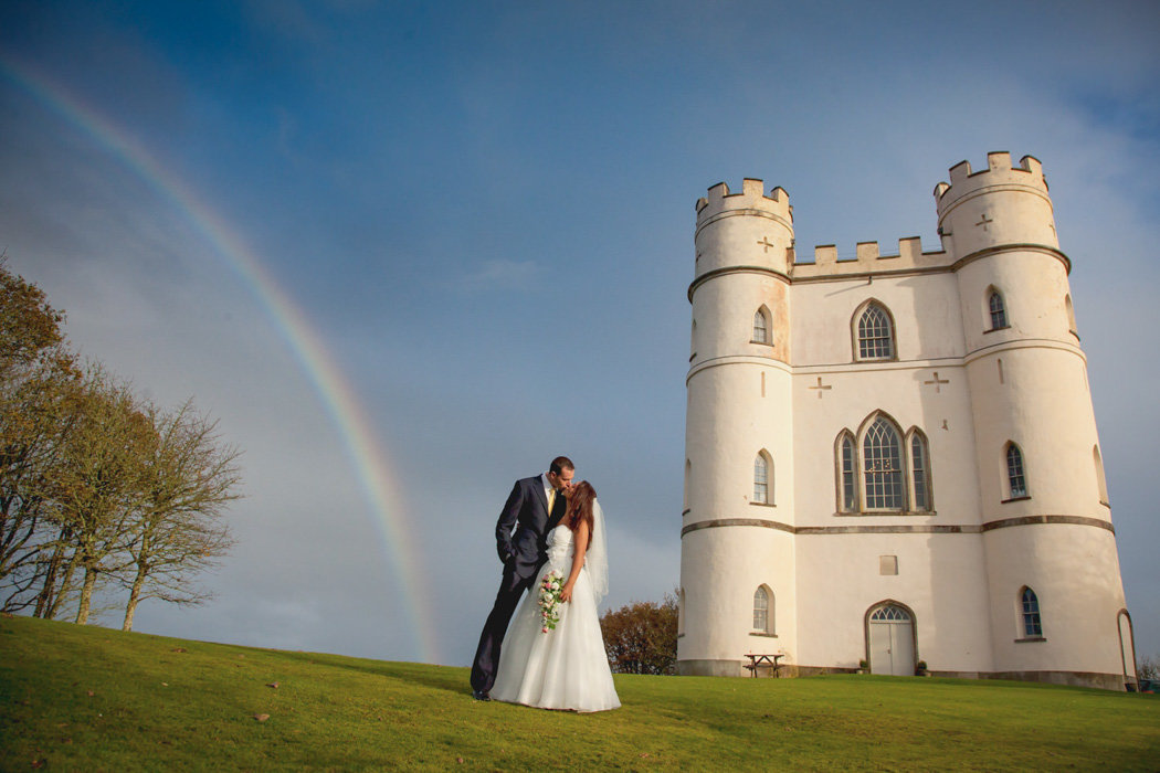 Wedding couple with stunning rainbow over Haldon Belvedere Wedding in Devon