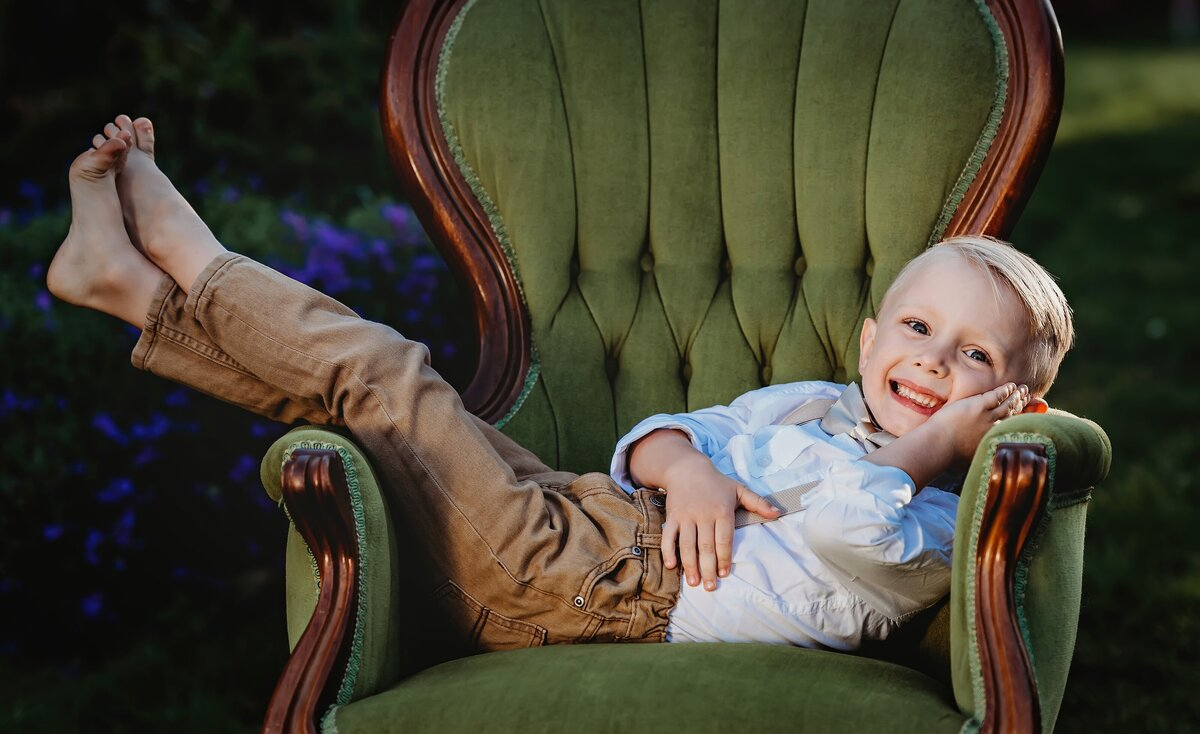 Young boy lays across a victorian green velvet chair and smiles