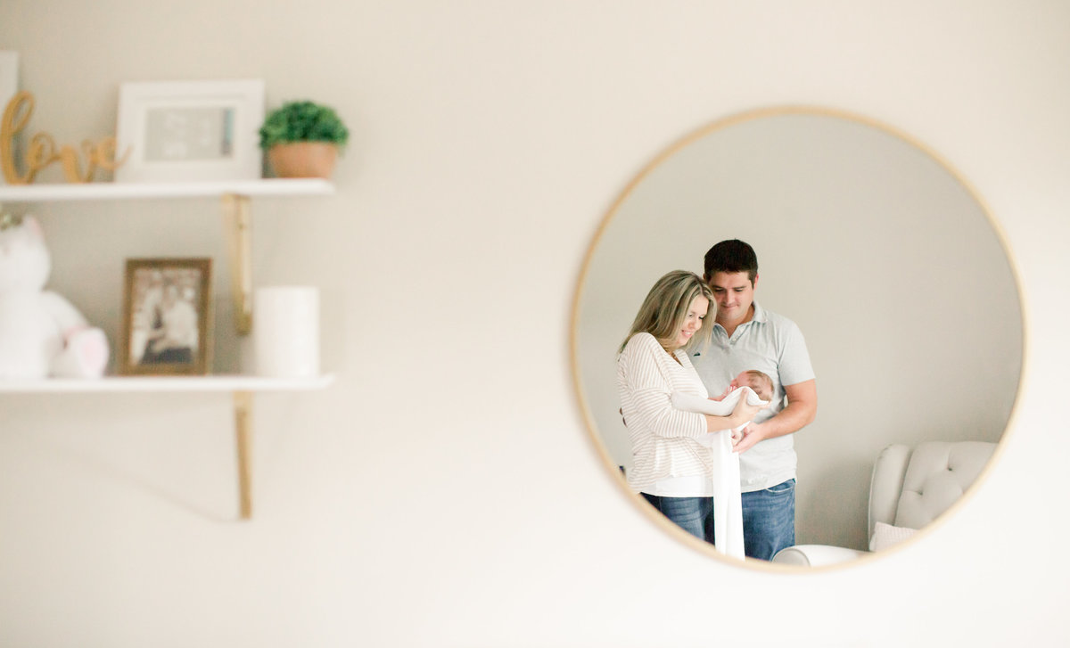 mom and dad holding daughter in reflection of circle mirror in nursery of home
