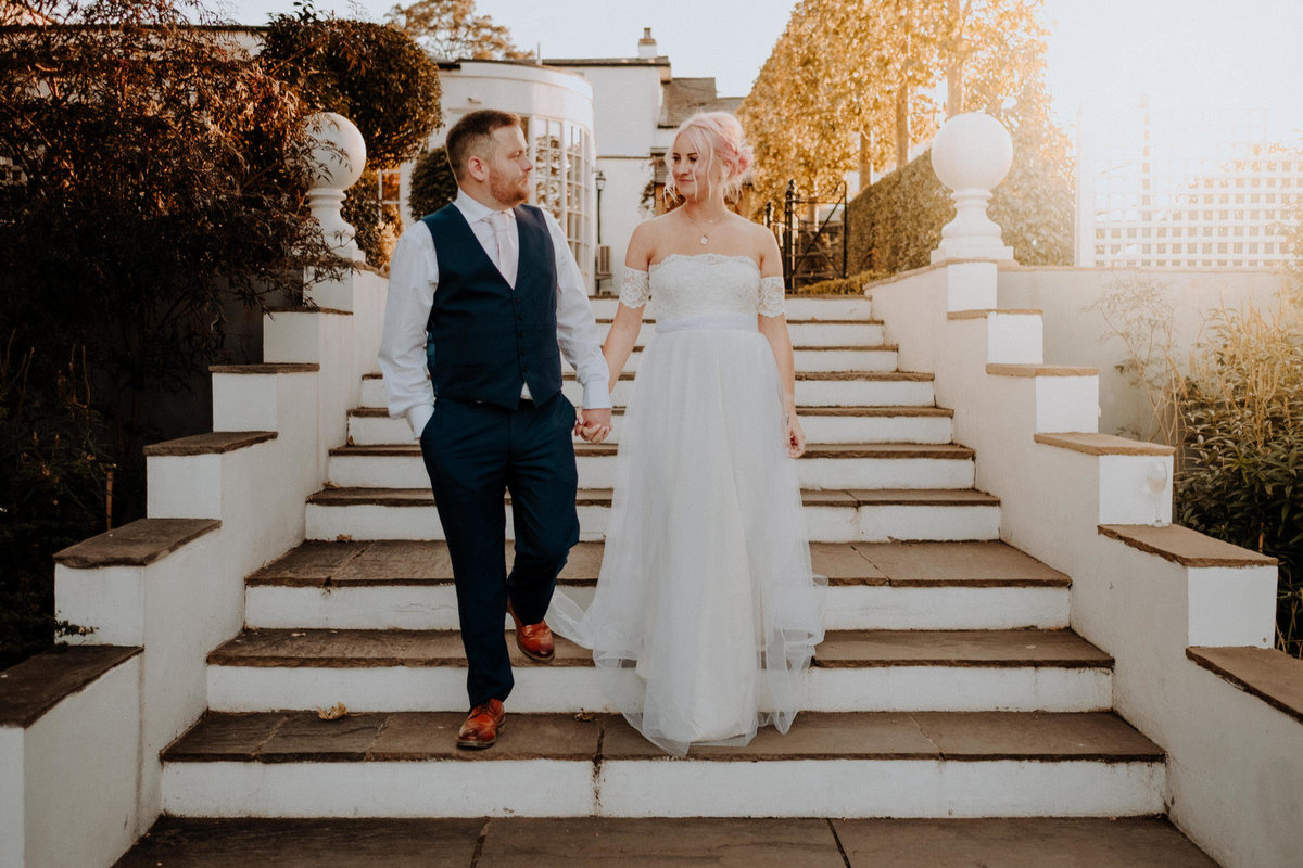 alternative wedding at warwick house in warwickshire of bride and groom walking down stairs at golden hour