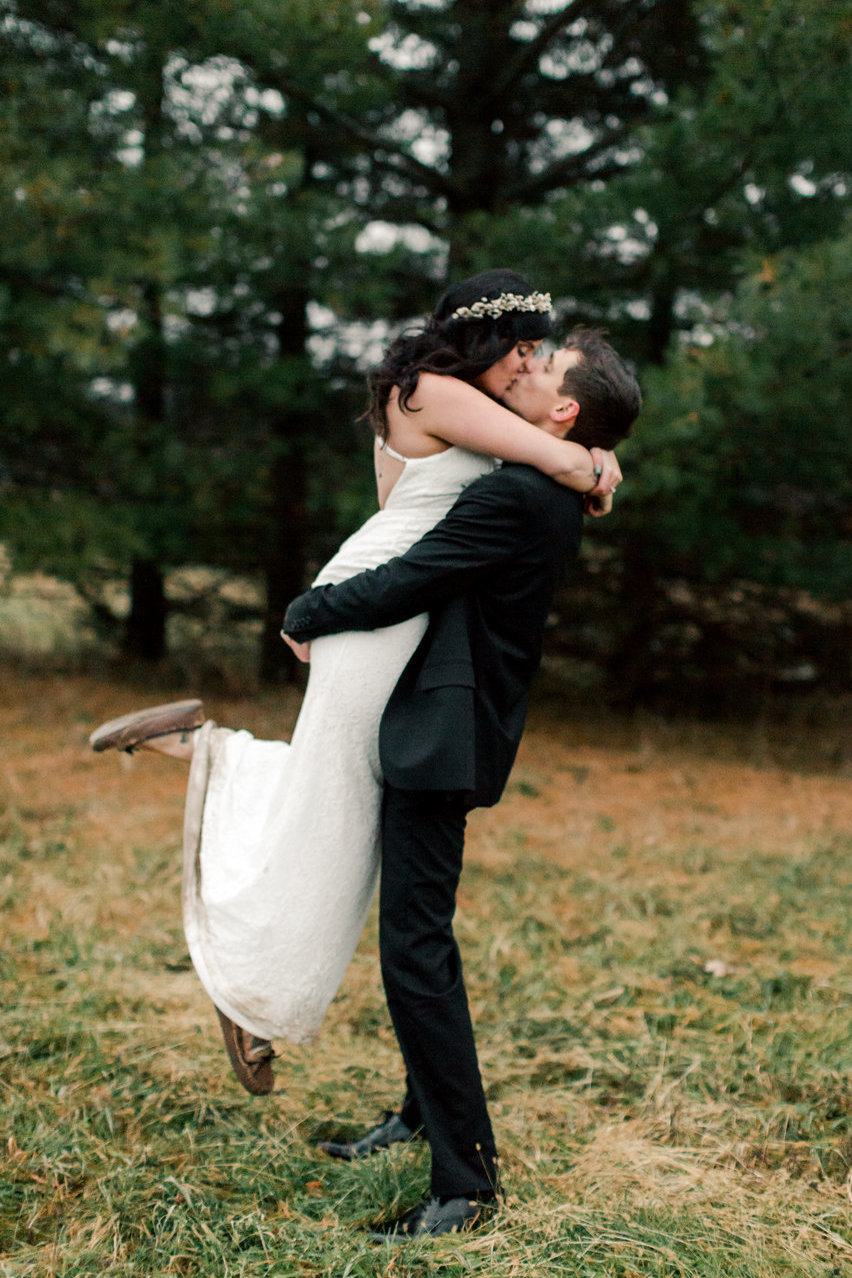 casual fall elopement in rochester minnesota pines and bride and groom kiss outdoors