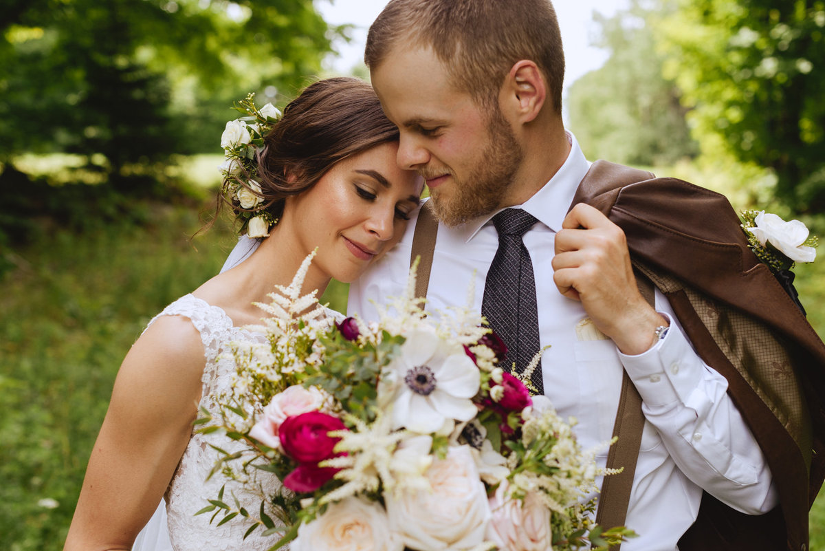 bride resting her head on grooms shoulder with beautiful wedding bouquet