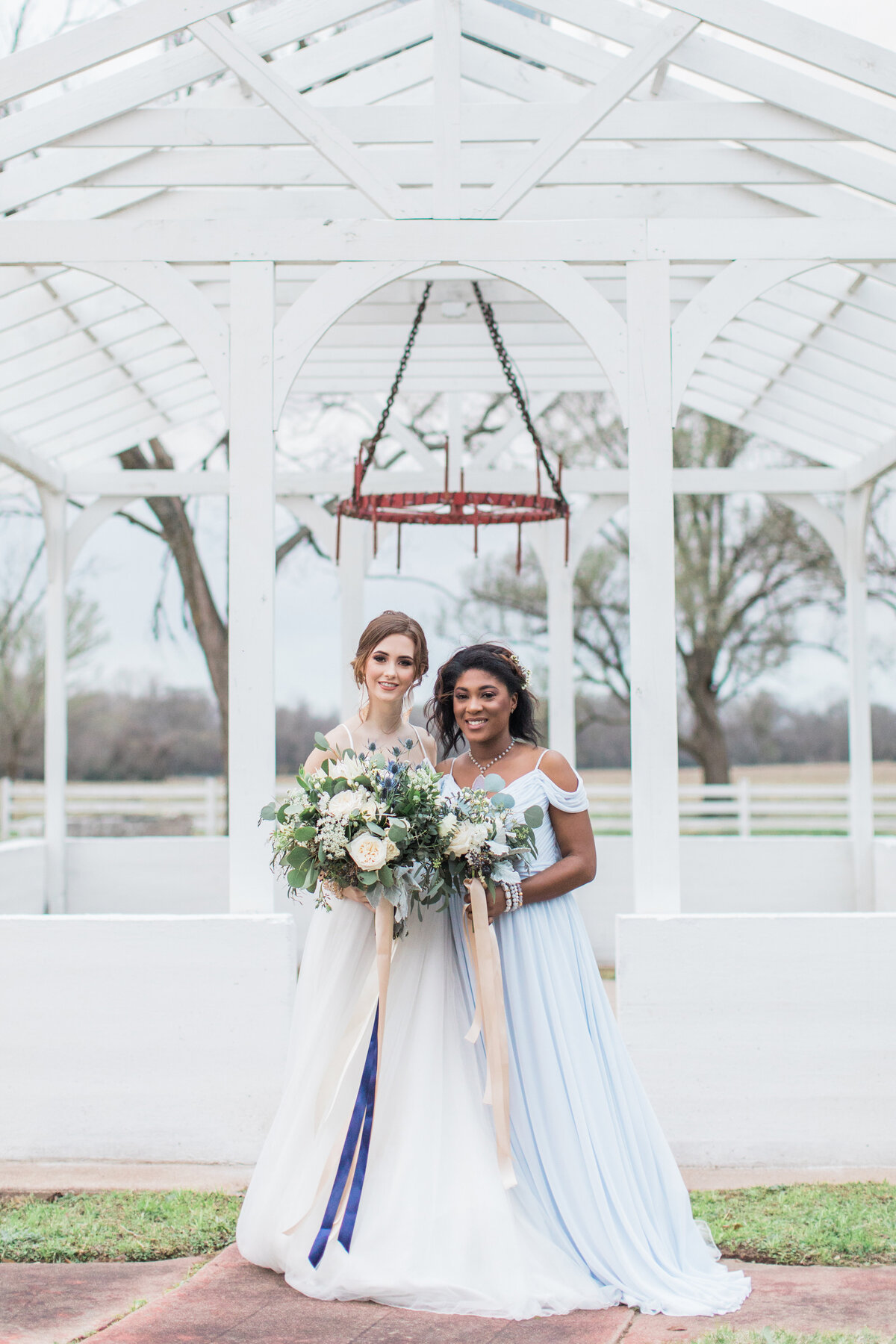 A bride and bridesmaid standing in front of the Greenhouse Arbor at the Grand Texana Wedding venue