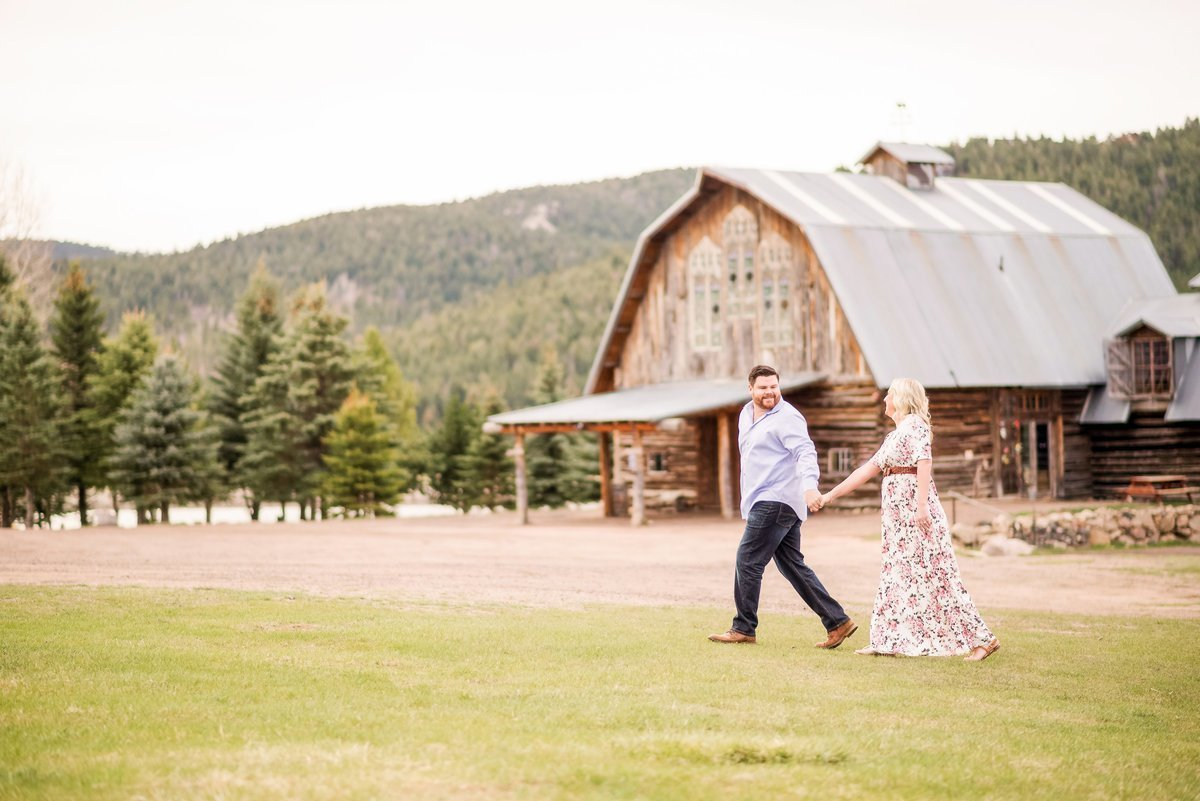 Engaged couple holds hands walking through a field in front of the barn at evergreen memorial park.