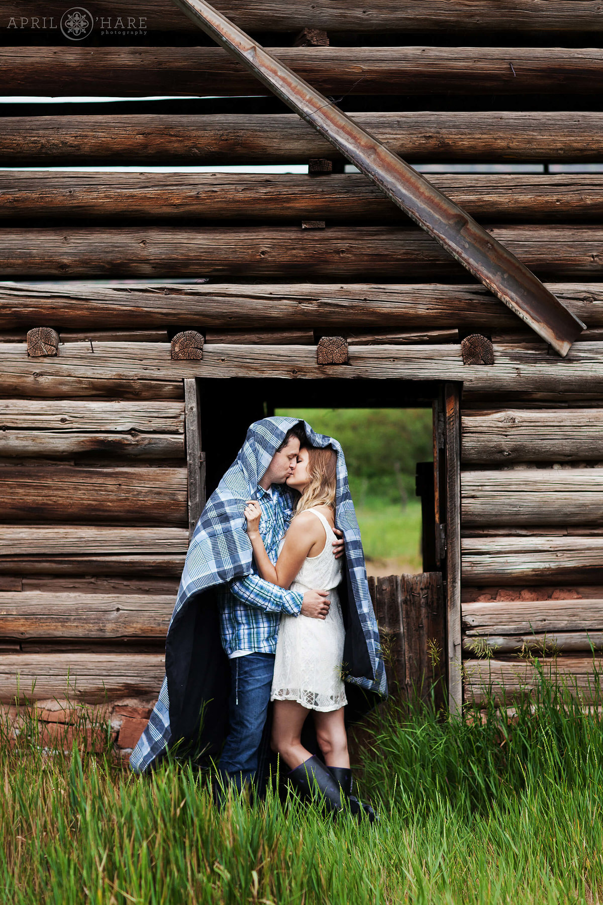 Cuddling under a blanket at a rustic barn engagement photography at Sylvan Lake State Park Eagle CO